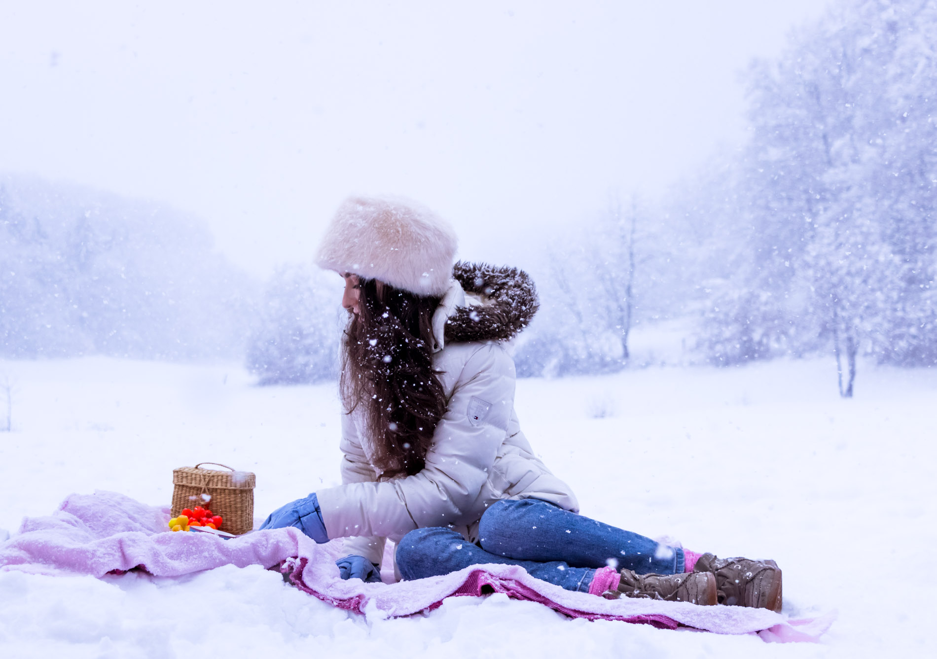 Fashion Blogger Veronika Lipar of Brunette from Wall Street wearing white down puffer jacket, blue jeans, blue snow gloves, white faux fur hat, pink wool socks and Isabel Marant Bobby sneakers for winter picnic in the snow