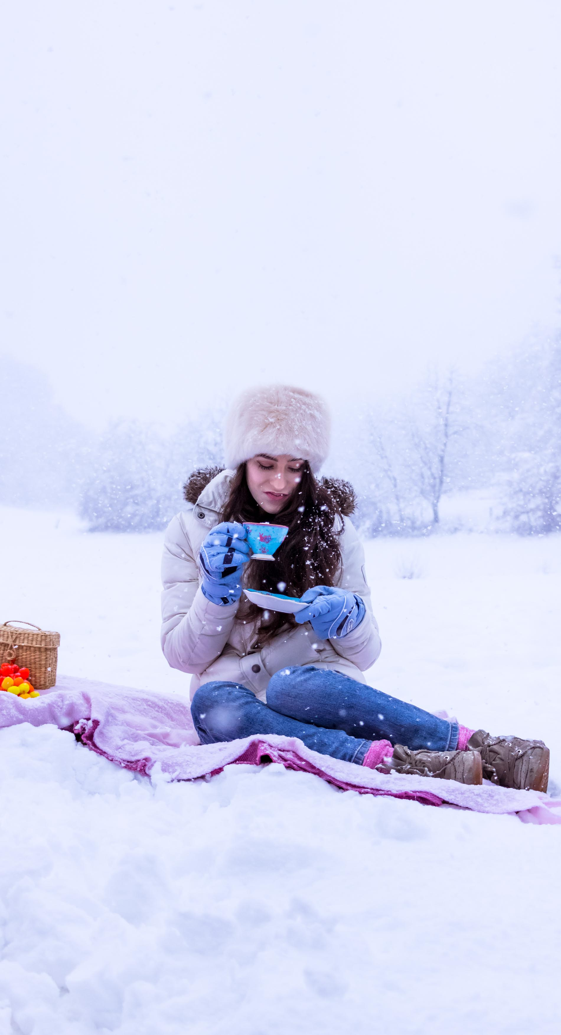 Fashion Blogger Veronika Lipar of Brunette from Wall Street wearing white down puffer jacket, blue jeans, blue snow gloves, white faux fur hat, pink wool socks and Isabel Marant Bobby sneakers, drinking tea while sitting in the snow