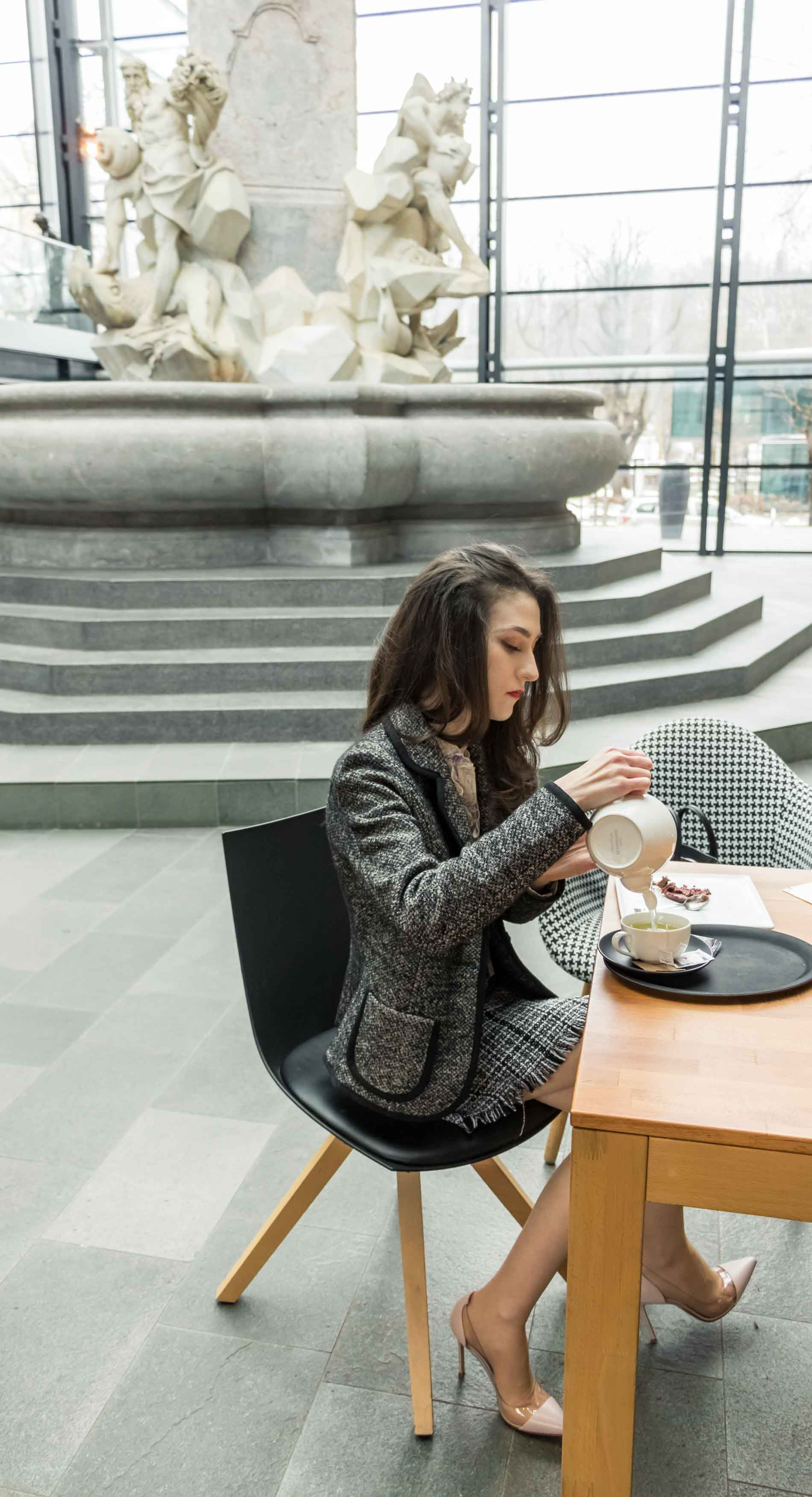 Fashion Blogger Veronika Lipar of Brunette from Wall Street dressed in tweed plaid mini skirt from Storets, black and white Marella tweed jacket, blush Gianvito Rossi Plexi 100 leather and PVC pumps, while pouring a tea