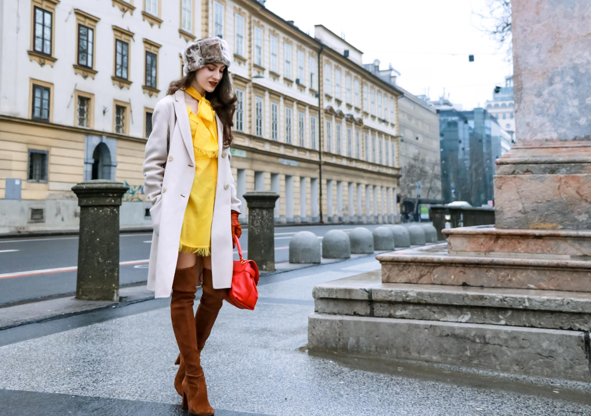 Fashion Blogger Veronika Lipar of Brunette from Wall Street dressed in the IT dress of spring summer 2018, the yellow dress from Escada, off-white, pastel double-breasted coat from Weekend Maxmara, pink top handle bag from See by Chloé, brown Stuart Weitzman over the knee boots, and faux fur headband in winter
