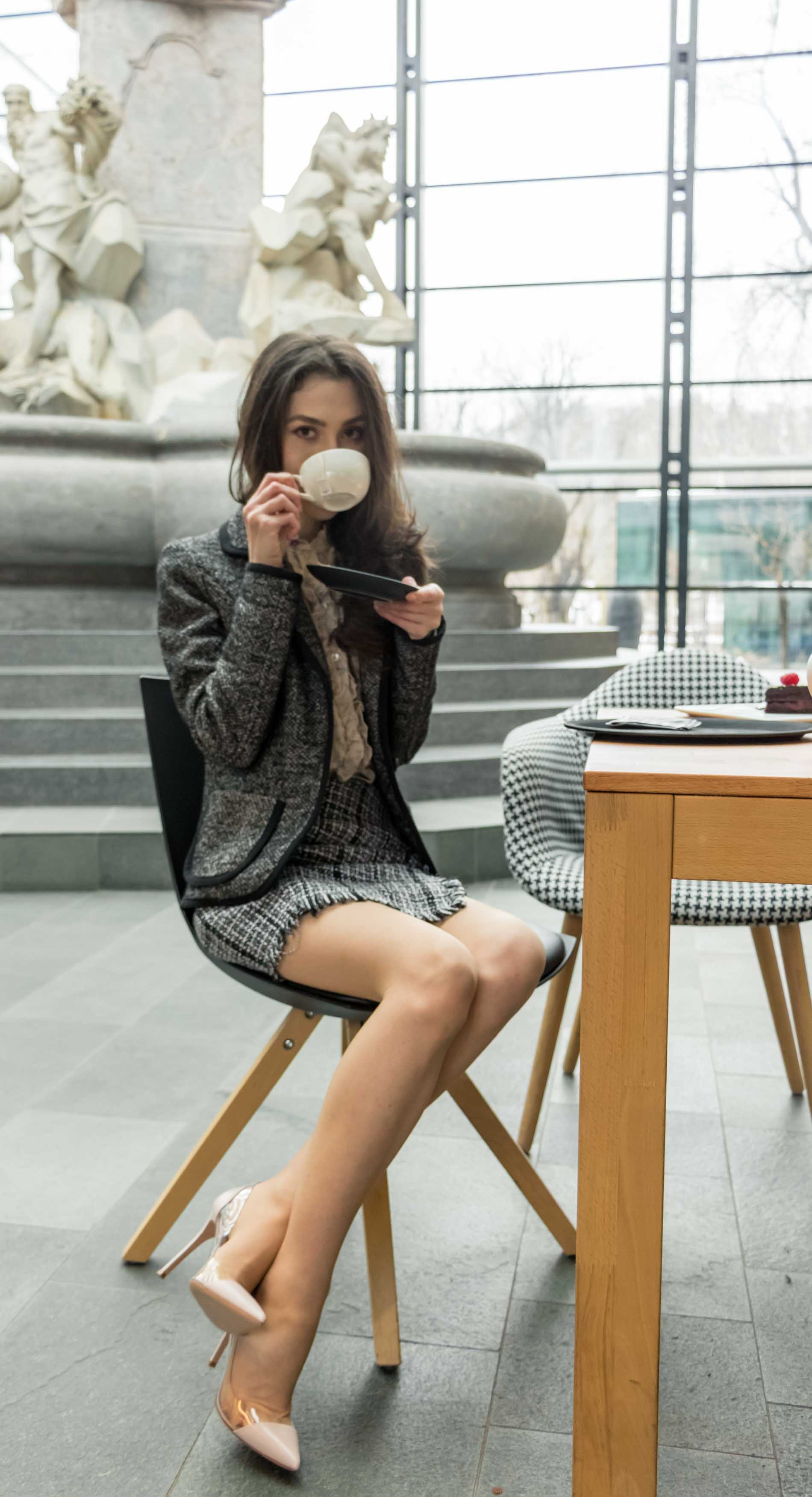 Fashion Blogger Veronika Lipar of Brunette from Wall Street dressed in tweed plaid mini skirt from Storets, black and white Marella tweed jacket, blush Gianvito Rossi Plexi 100 leather and PVC pumps, while drinking coffee