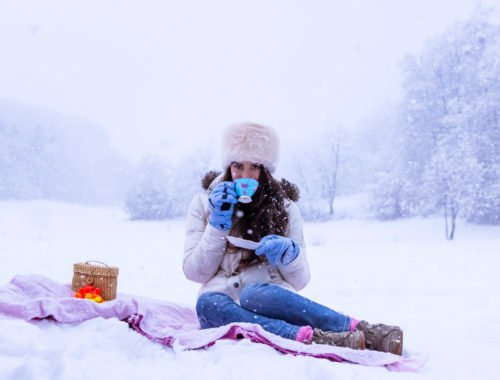 Fashion Blogger Veronika Lipar of Brunette from Wall Street dressed in white down puffer jacket, blue jeans, blue snow gloves, white faux fur hat, pink wool socks and Isabel Marant Bobby sneakers, drinking tea while sitting in the snow on a picnic blanket