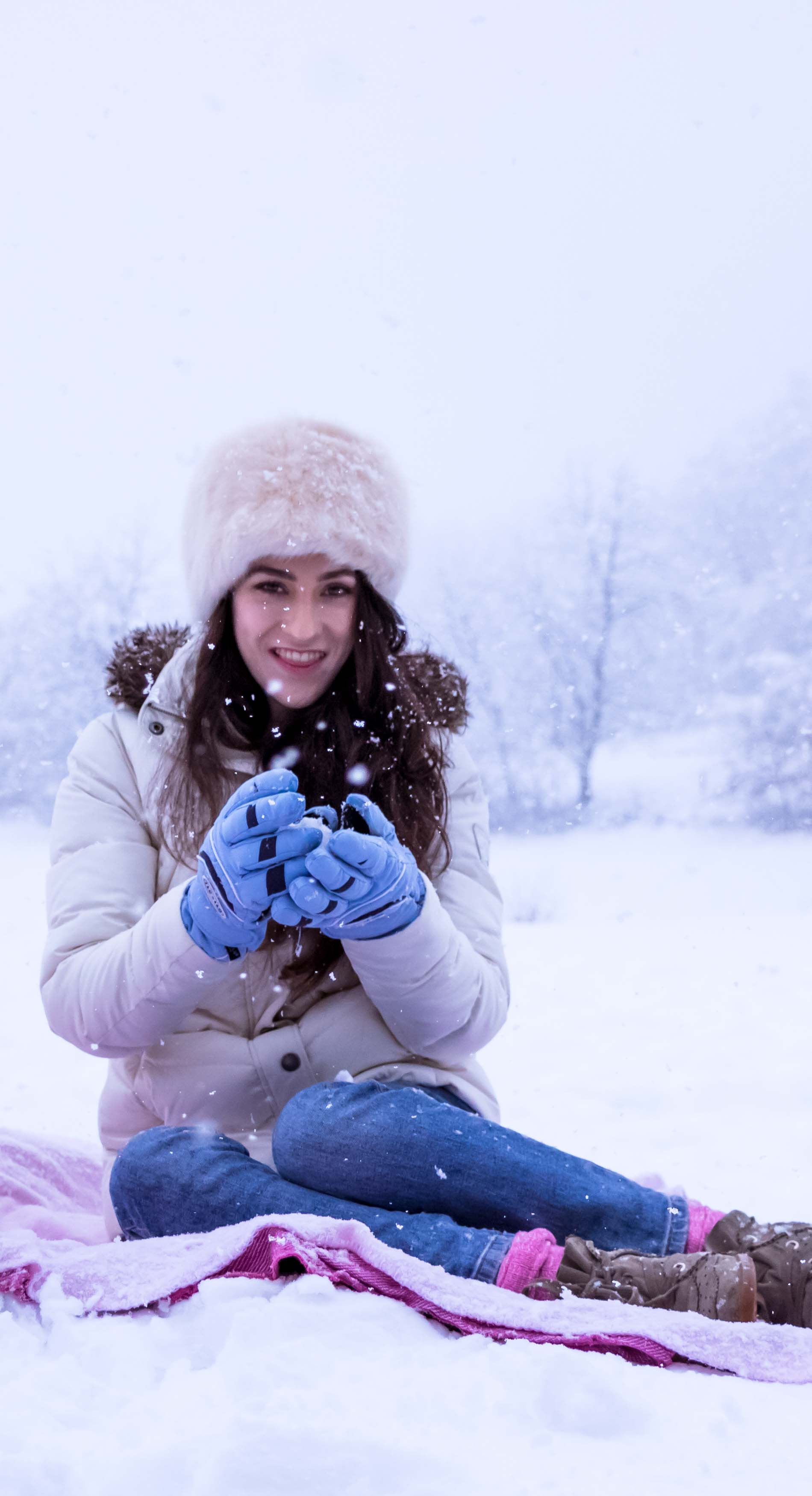 Fashion Blogger Veronika Lipar of Brunette from Wall Street dressed in white down puffer jacket, blue jeans, blue snow gloves, white faux fur hat, pink wool socks and Isabel Marant Bobby sneakers for winter picnic in the snow