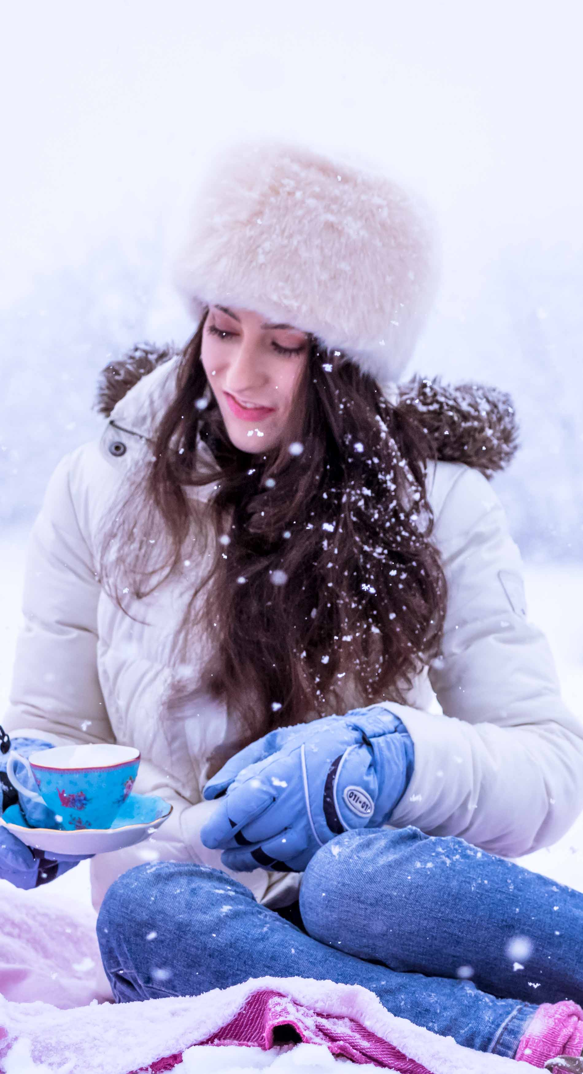 Fashion Blogger Veronika Lipar of Brunette from Wall Street wearing white down puffer jacket, blue jeans, blue snow gloves, white faux fur hat, pink wool socks and Isabel Marant Bobby sneakers, holding tea cup in the snow