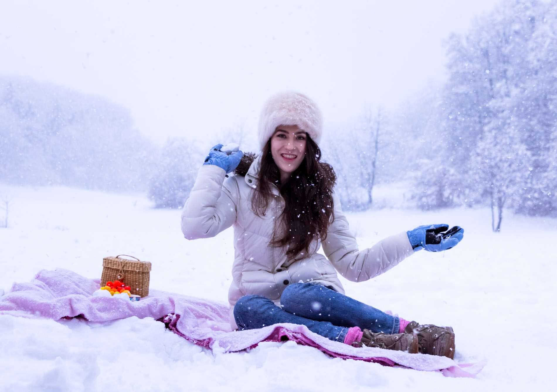 Fashion Blogger Veronika Lipar of Brunette from Wall Street wearing white down puffer jacket, blue jeans, blue snow gloves, white faux fur hat, pink wool socks and Isabel Marant Bobby sneakers, throwing snowballs