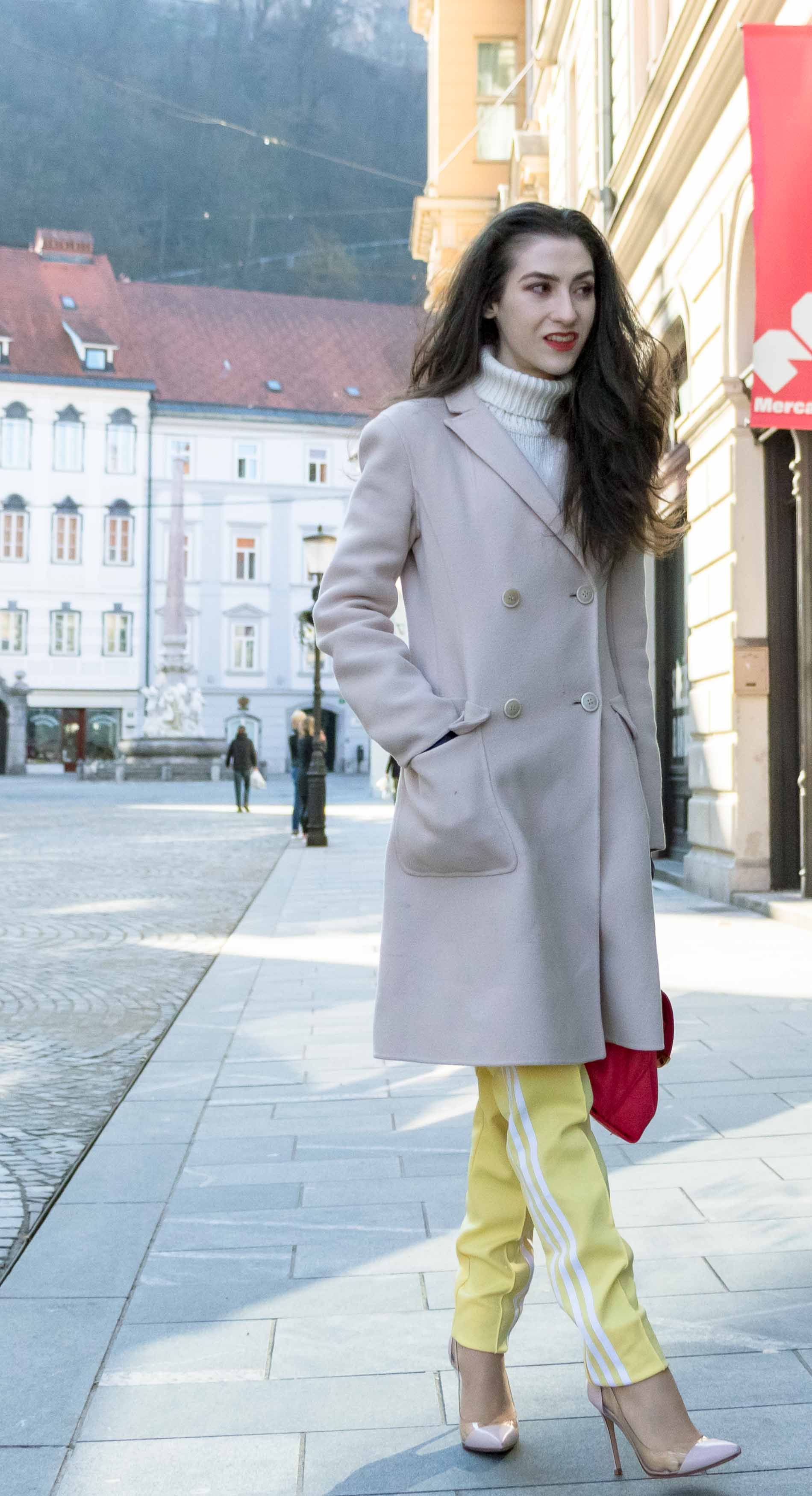 Fashion Blogger Veronika Lipar of Brunette from Wall Street dressed in yellow track pants with white stripes from Adidas, white turtleneck knit sweater, off-white pastel double breasted coat from Weekend Max Mara, blush powder transparent plexi shoes from Gianvito Rossi, pink top handle bag from See by Chloe while walking down the street in Ljubljana