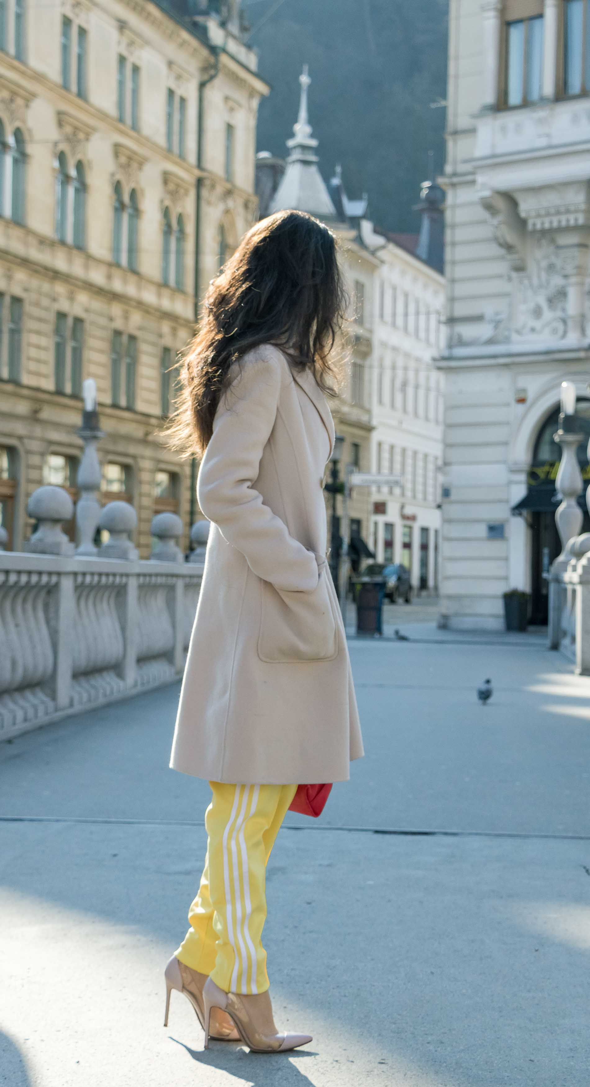 - Fashion Blogger Veronika Lipar of Brunette from Wall Street wearing yellow track pants with white stripes from Adidas, white turtleneck knit sweater, off-white pastel double breasted coat from Weekend Max Mara, blush powder transparent plexi shoes from Gianvito Rossi, pink top handle bag from See by Chloe while standing on the bridge in Ljubljana