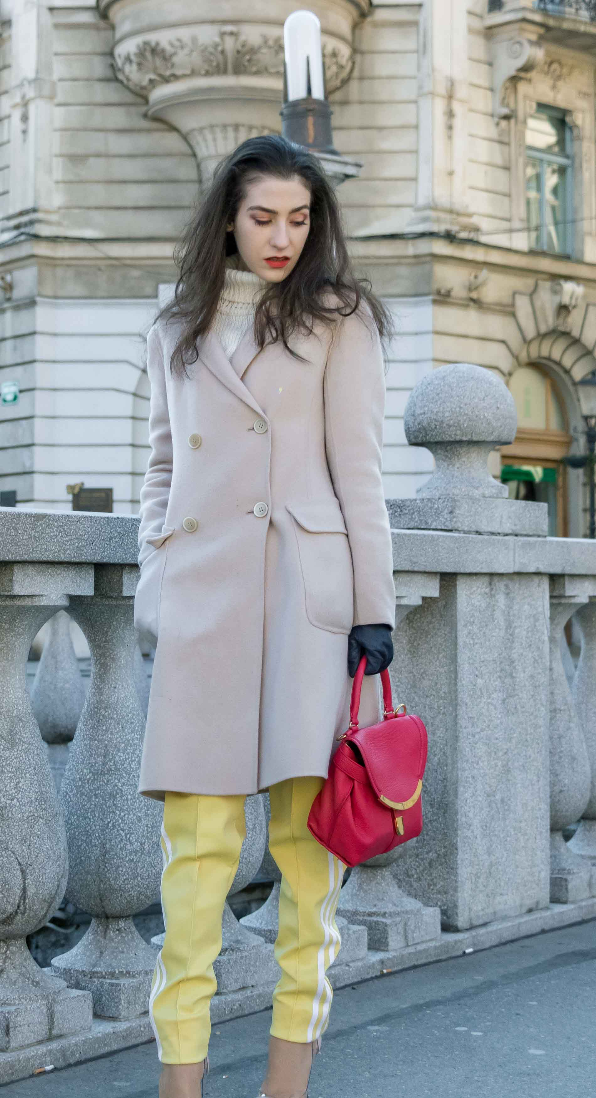 Fashion Blogger Veronika Lipar of Brunette from Wall Street dressed in yellow track pants with white stripes from Adidas, white turtleneck knit sweater, off-white pastel double breasted coat from Weekend Max Mara, blush powder transparent plexi pumps shoes from Gianvito Rossi, pink top handle bag from See by Chloe while standing on the bridge in Ljubljana on a cold spring day