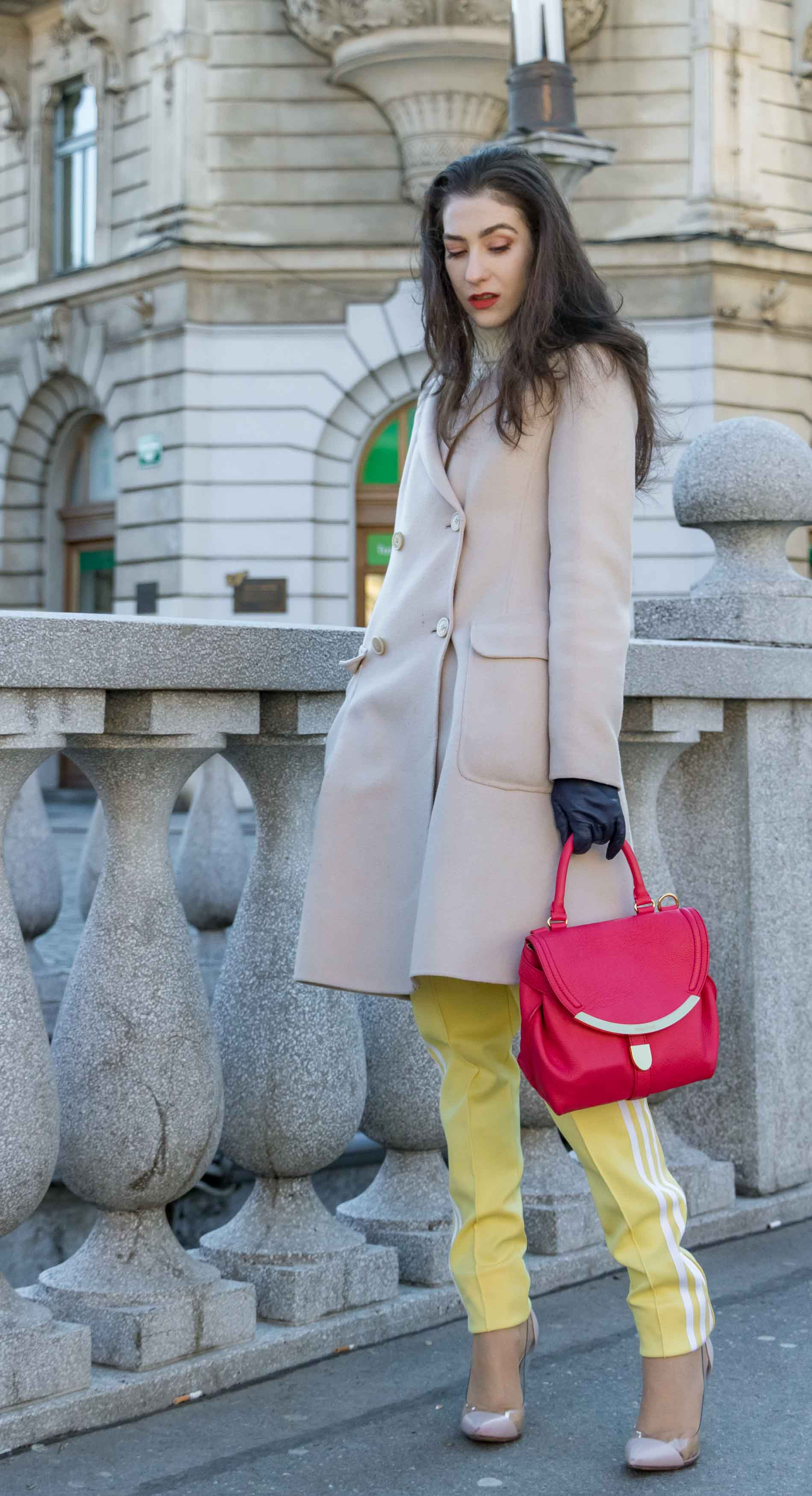 Fashion Blogger Veronika Lipar of Brunette from Wall Street wearing yellow track pants with white stripes from Adidas, white turtleneck knit sweater, off-white pastel double breasted coat from Weekend Max Mara, blush powder transparent plexi pumps from Gianvito Rossi, pink top handle bag from See by Chloe while standing on the bridge in Ljubljana on a cold spring day