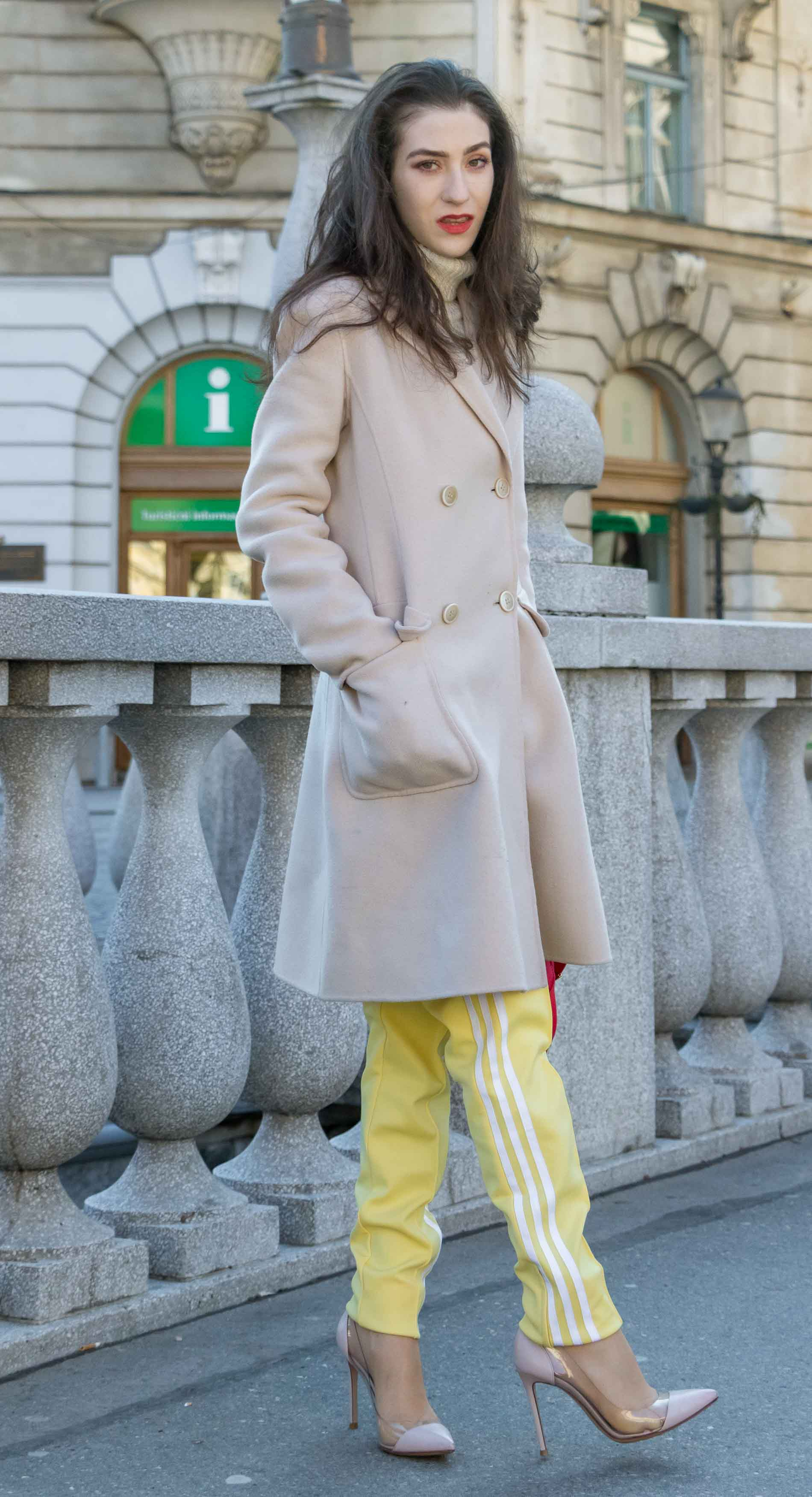 Fashion Blogger Veronika Lipar of Brunette from Wall Street wearing yellow track pants with white stripes from Adidas, white turtleneck knit sweater, off-white pastel double breasted coat from Weekend Max Mara, blush powder transparent plexi shoes from Gianvito Rossi, pink top handle bag from See by Chloe while standing on the bridge in Ljubljana