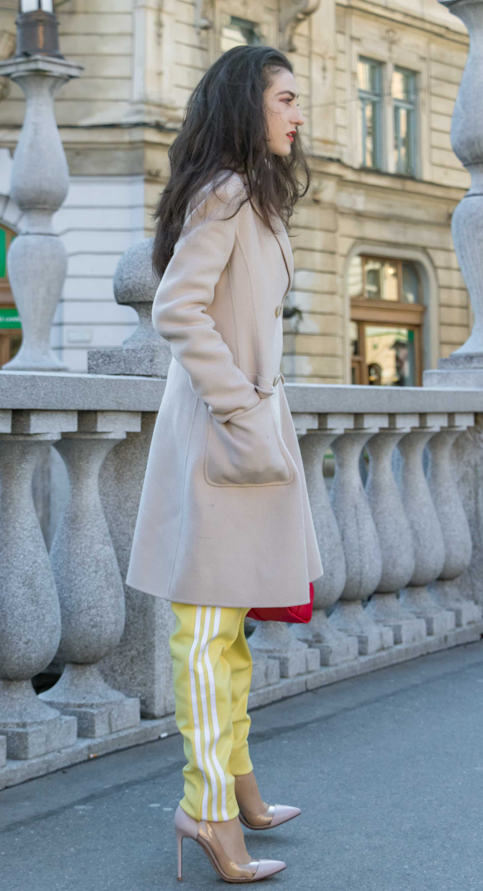 Fashion Blogger Veronika Lipar of Brunette from Wall Street dressed in yellow track pants with white stripes from Adidas, white turtleneck knit sweater, off-white pastel double breasted coat from Weekend Max Mara, blush powder transparent plexi shoes from Gianvito Rossi, pink top handle bag from See by Chloe while standing on the bridge in Ljubljana