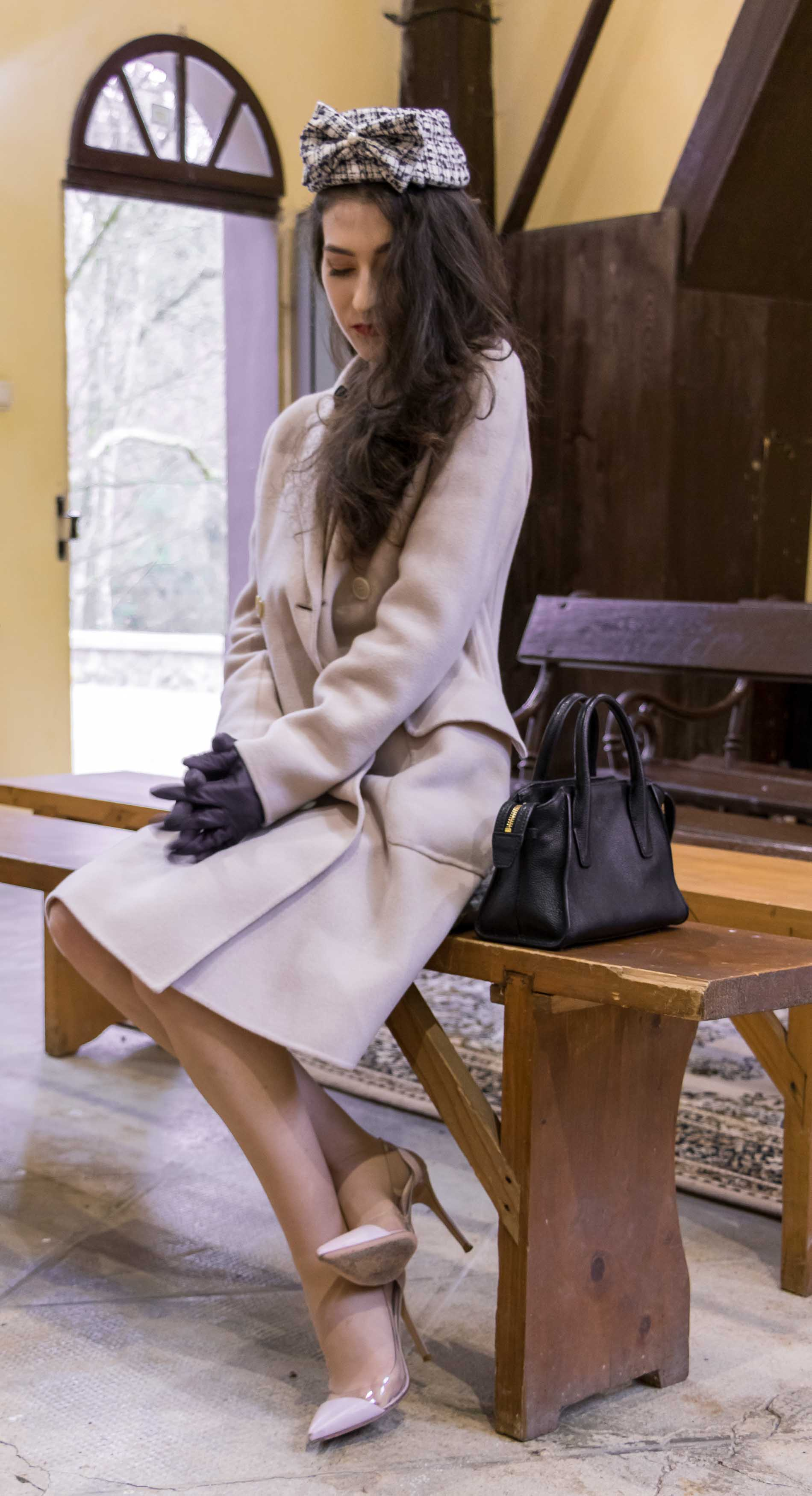 Fashion Blogger Veronika Lipar of Brunette from Wall Street dressed in Weekend Maxmara off-white pastel coat, Gianvito Rossi plexi pumps, small black top handle bag and headwear in church