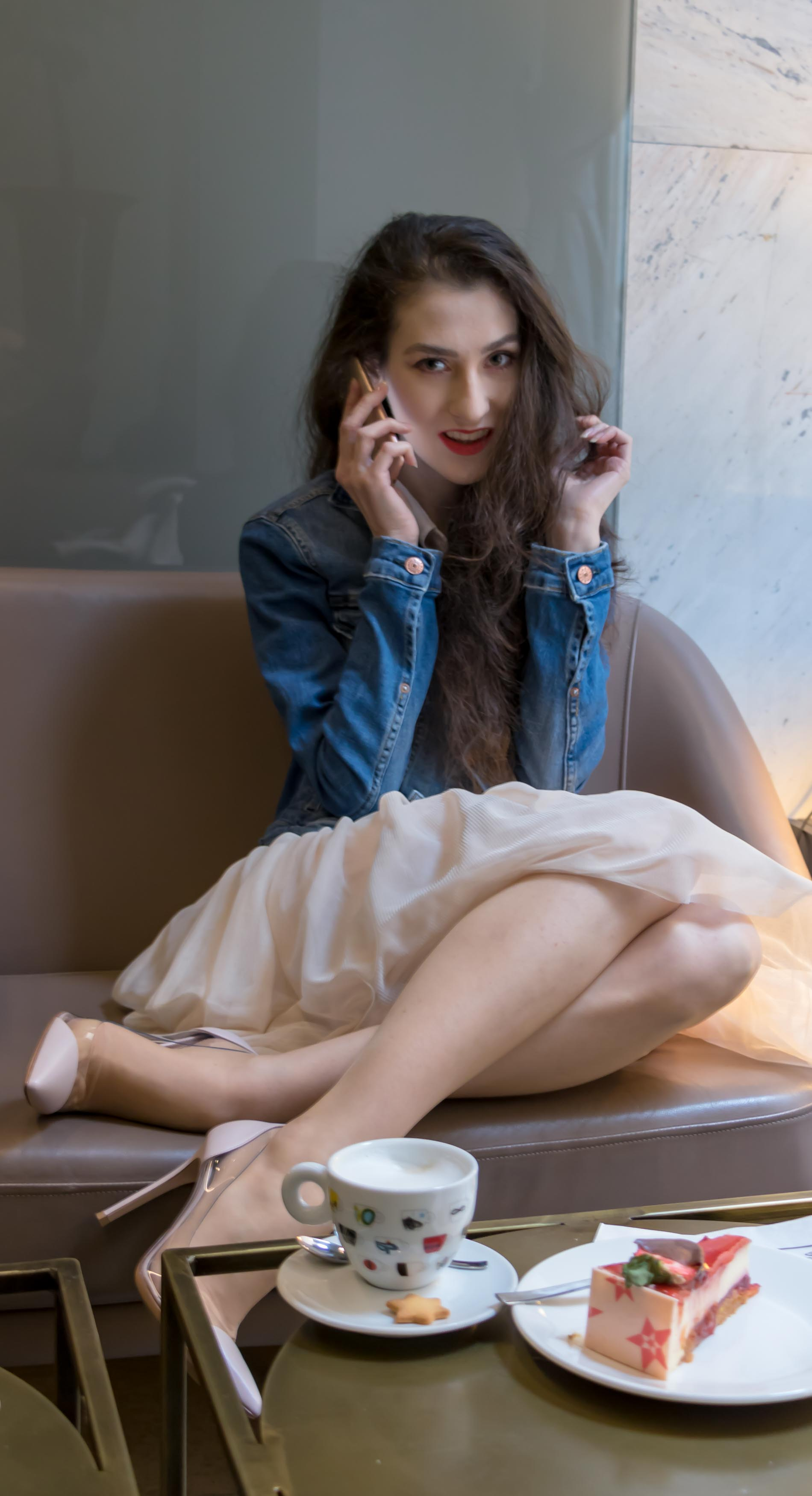 Fashion Blogger Veronika Lipar of Brunette from Wall Street wearing blush Gianvito Rossi Plexi 100 leather and PVC pump shoes, blush tulle skirt from Zara, blue denim jacket from H&M while talking with her squad on iPhone