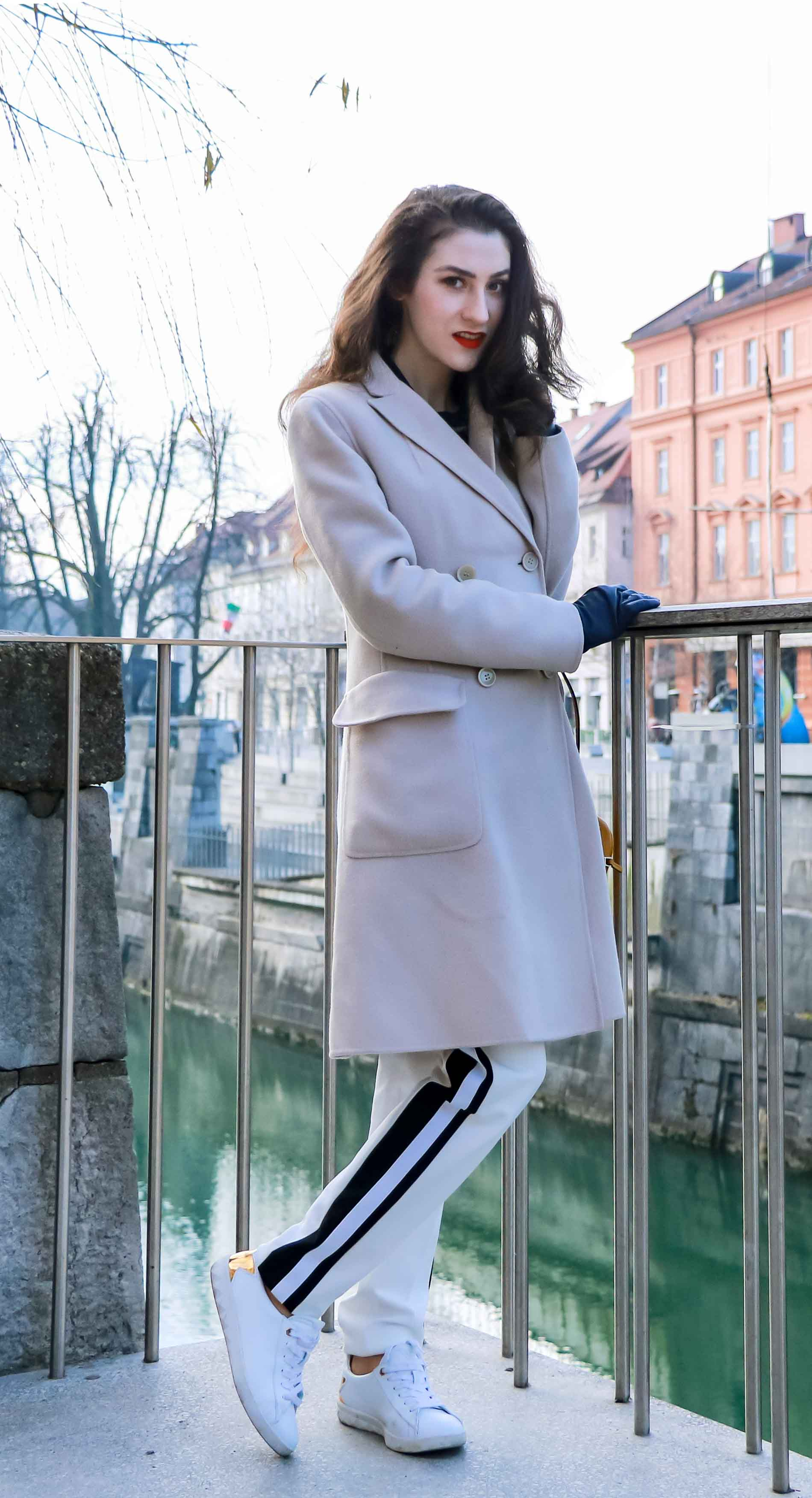 Fashion Blogger Veronika Lipar of Brunette from Wall Street wearing white track pants with black side stripe from Escada, black silk blouse, off-white pastel double breasted coat from Weekend Max Mara, white leather sneakers from Diesel, yellow shoulder bag from Escada while standing above the river Ljubljanica in Ljubljana