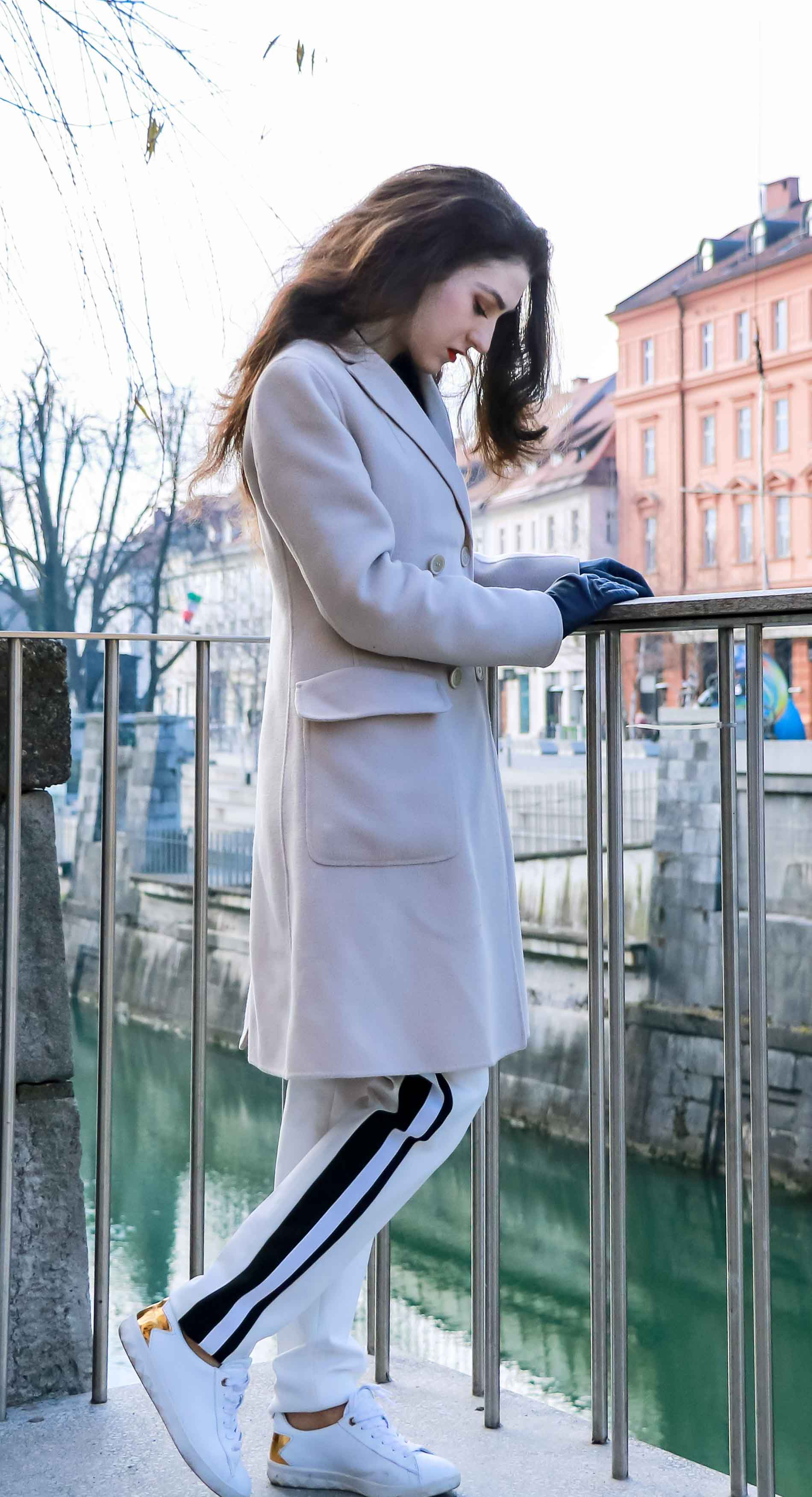 - Fashion Blogger Veronika Lipar of Brunette from Wall Street wearing white track pants with black side stripe from Escada, black silk blouse, off-white pastel double breasted coat from Weekend Max Mara, white leather sneakers from Diesel, yellow shoulder bag from Escada while standing above the river Ljubljanica in Ljubljana