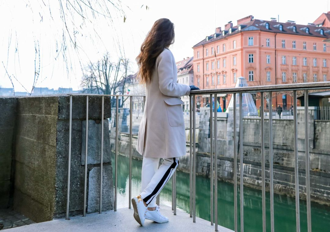 Fashion Blogger Veronika Lipar of Brunette from Wall Street dressed in white track pants with black side stripe from Escada, black silk blouse, off-white pastel double breasted coat from Weekend Max Mara, white leather sneakers from Diesel, yellow shoulder bag from Escada while standing above the river Ljubljanica in Ljubljana