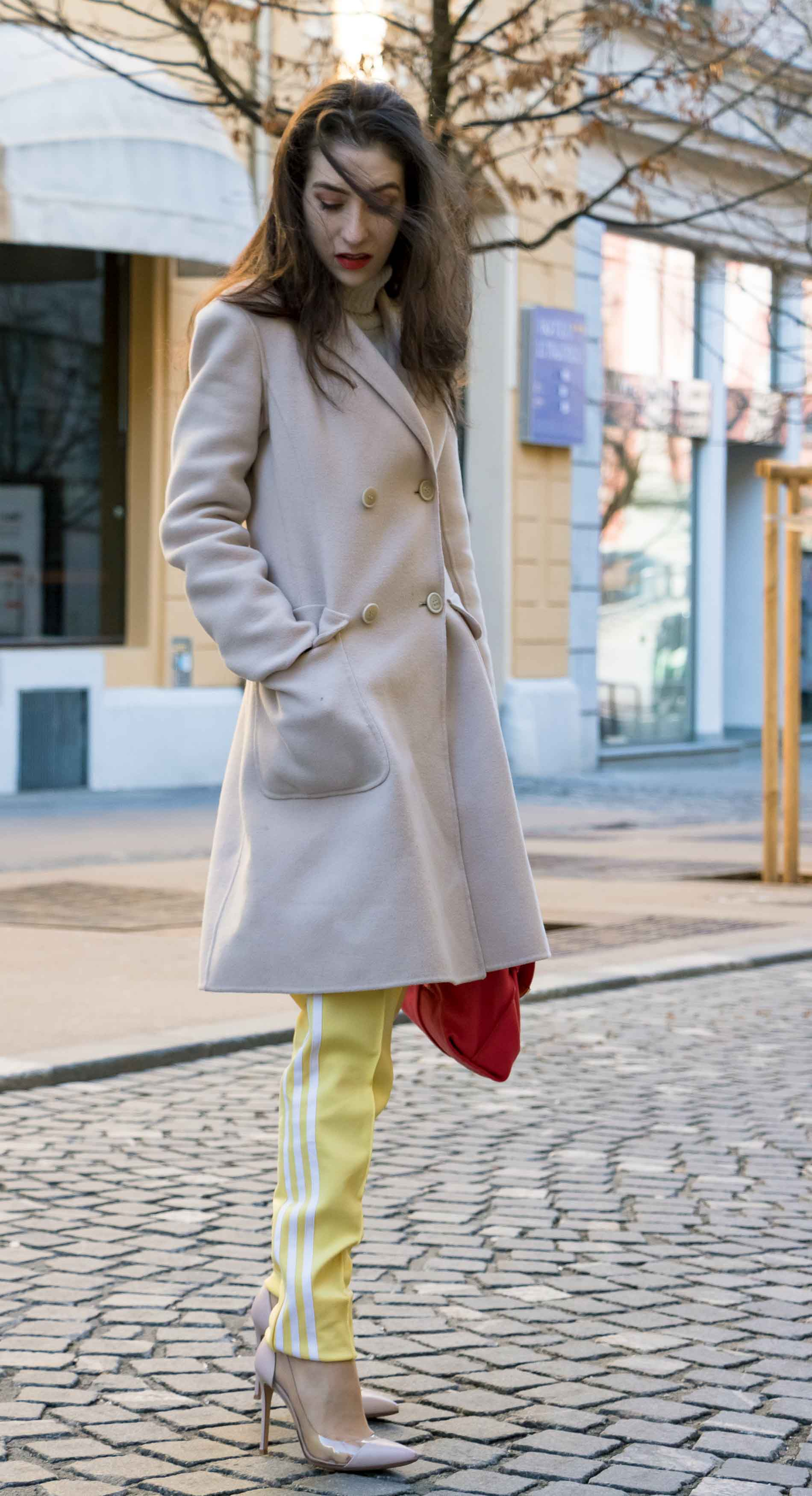 Fashion Blogger Veronika Lipar of Brunette from Wall Street dressed in yellow track pants with white stripes from Adidas, white turtleneck knit sweater, off-white pastel double breasted coat from Weekend Max Mara, blush powder transparent plexi pumps shoes from Gianvito Rossi, pink top handle bag from See by Chloe while standing on the street in Ljubljana on a cold spring day