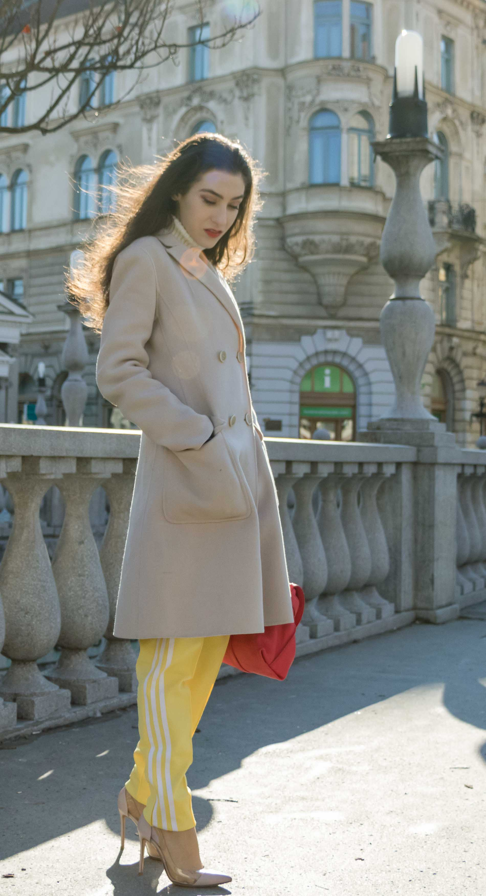 Fashion Blogger Veronika Lipar of Brunette from Wall Street wearing yellow track pants with white stripes from Adidas, white turtleneck knit sweater, off-white pastel double breasted coat from Weekend Max Mara, blush powder transparent plexi pumps shoes from Gianvito Rossi, pink top handle bag from See by Chloe while standing on the street in Ljubljana on a cold spring day