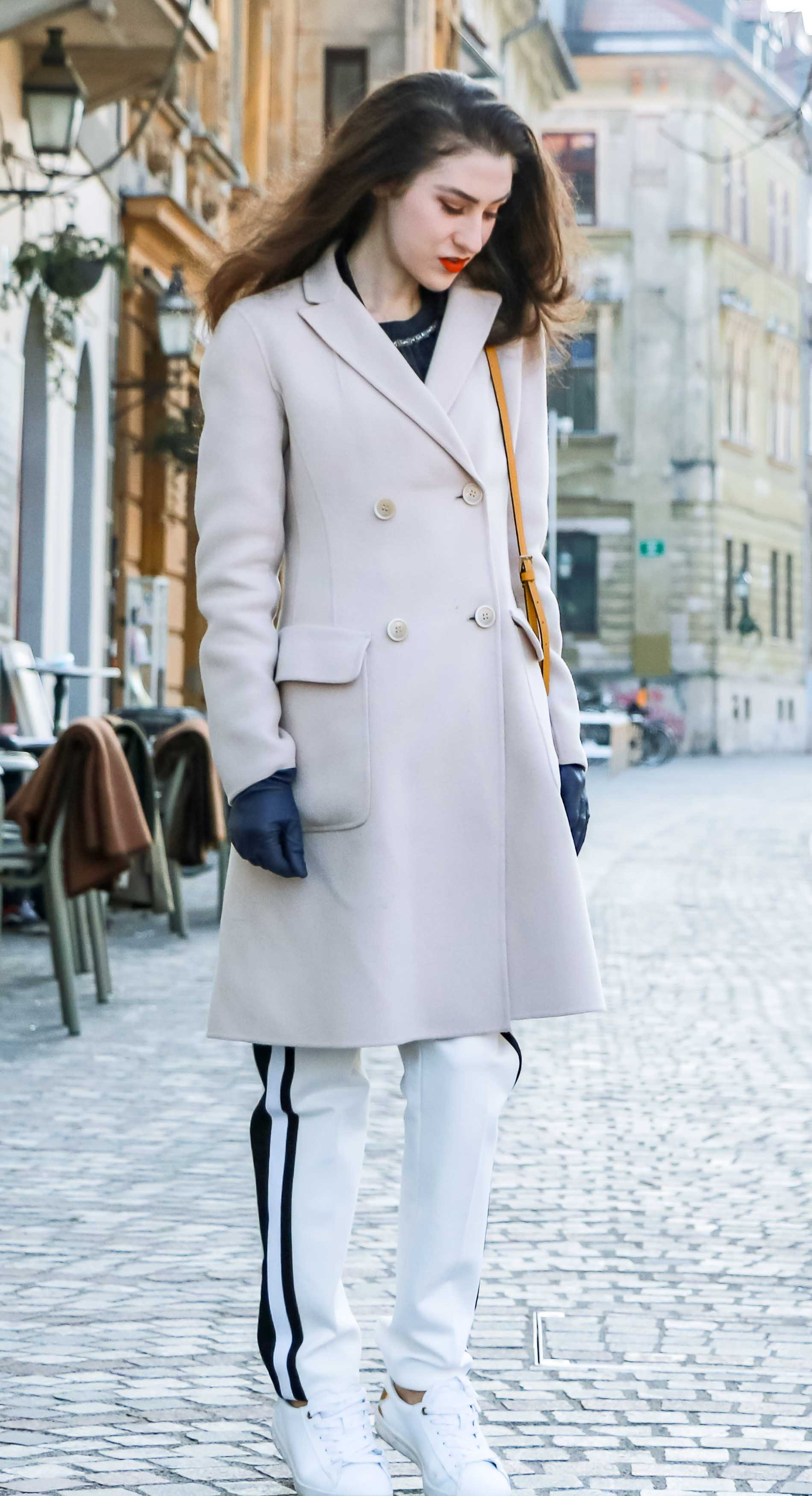 - Fashion Blogger Veronika Lipar of Brunette from Wall Street dressed in white track pants with black side stripe from Escada, black silk blouse, off-white pastel double breasted coat from Weekend Max Mara, white leather sneakers from Diesel, yellow shoulder bag from Escada while standing on the street in Ljubljana