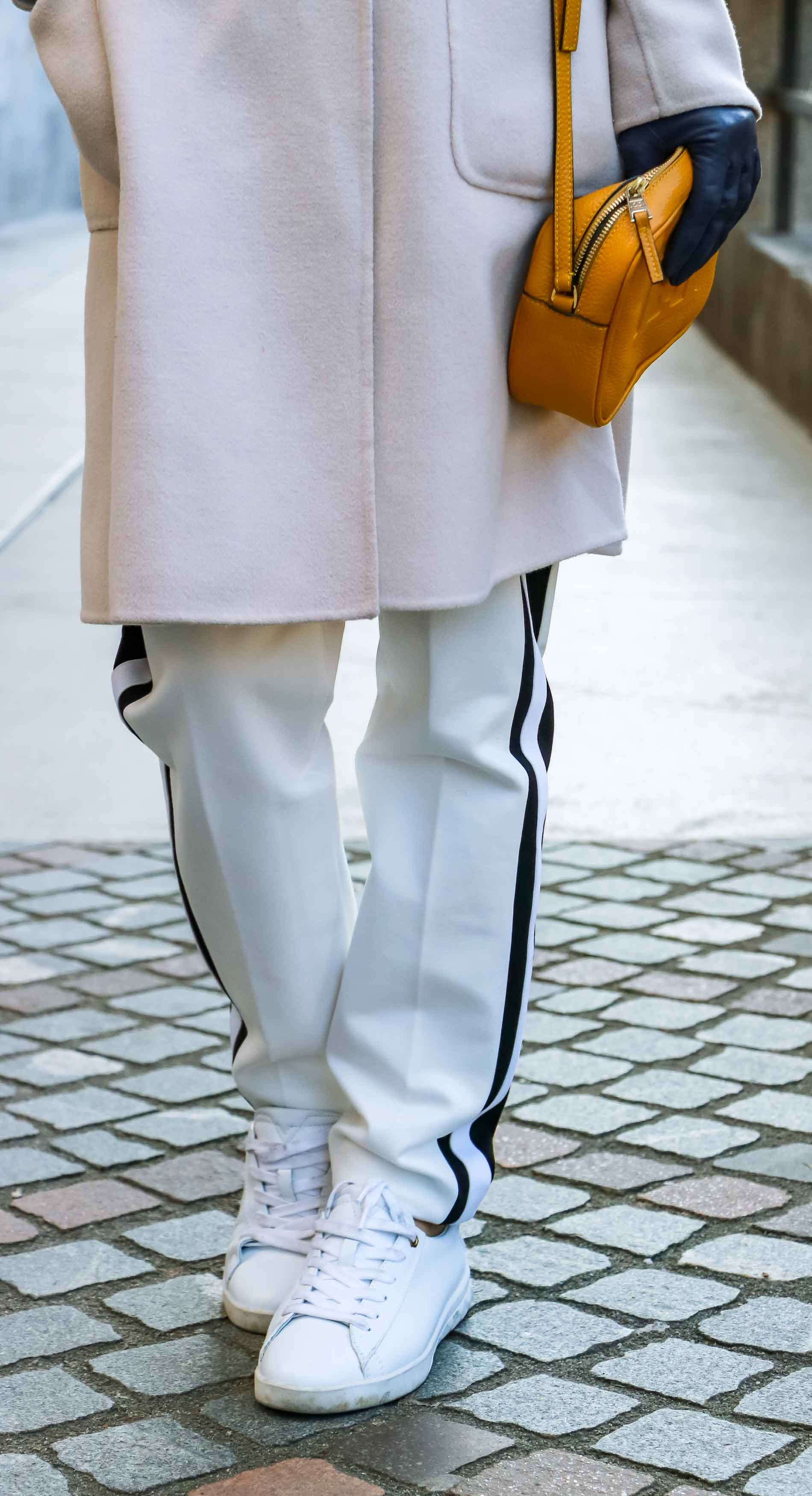 Fashion Blogger Veronika Lipar of Brunette from Wall Street dressed in white track pants with black side stripe from Escada, white leather sneakers from Diesel