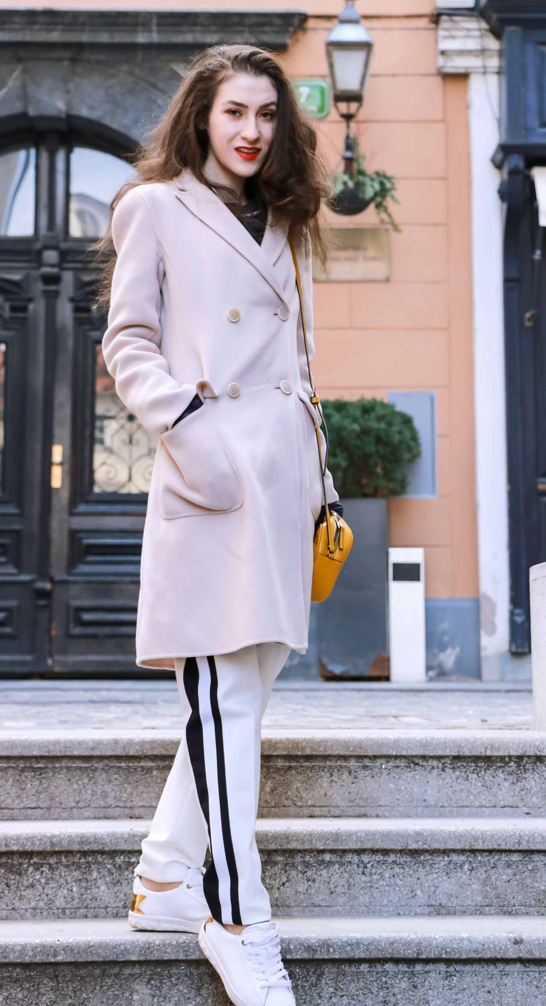 Fashion Blogger Veronika Lipar of Brunette from Wall Street wearing white track pants with black side stripe from Escada, black silk blouse, off-white pastel double breasted coat from Weekend Max Mara, white leather sneakers from Diesel, yellow shoulder bag from Escada while walking down the stairs in Ljubljana