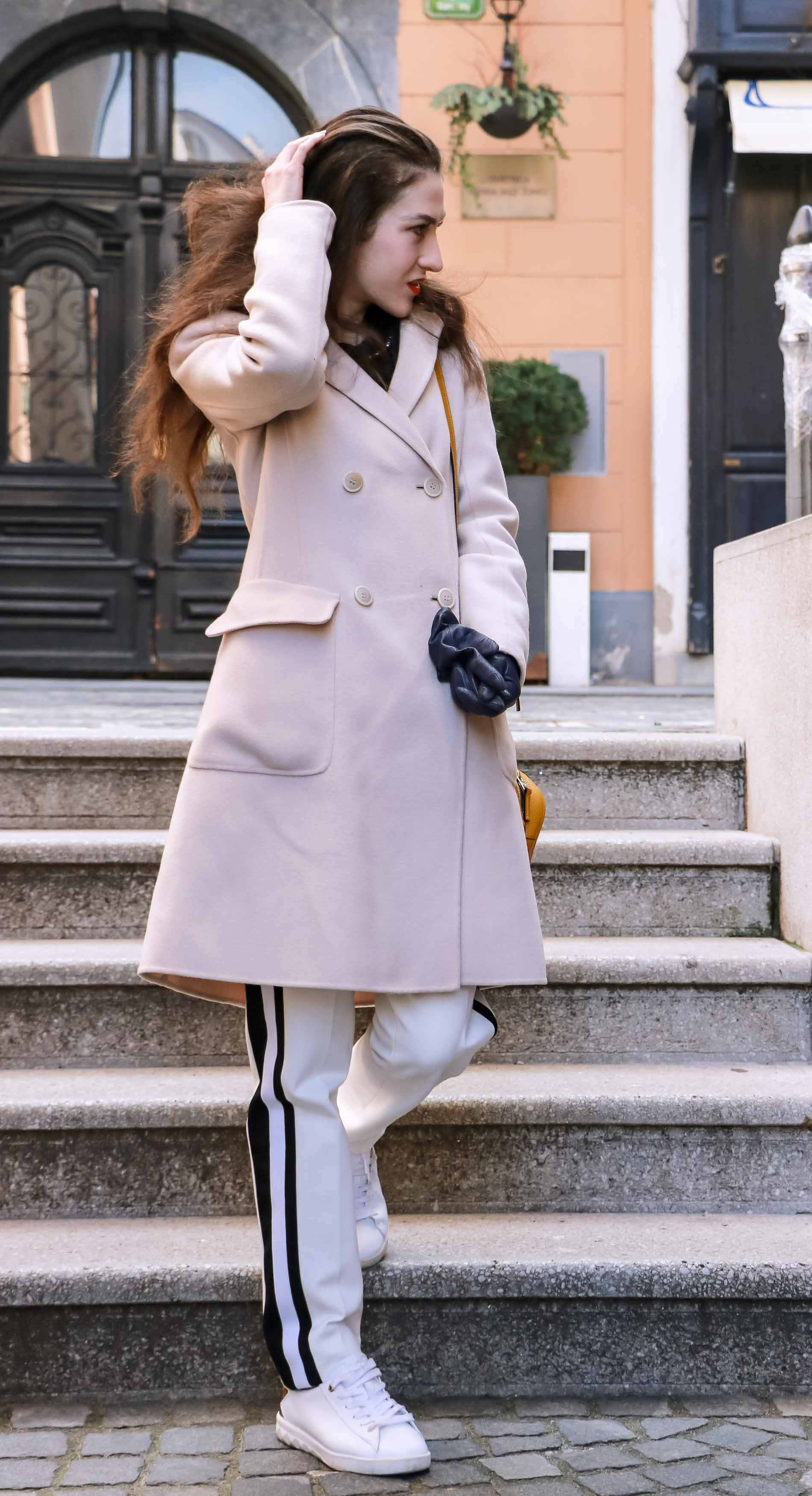 Fashion Blogger Veronika Lipar of Brunette from Wall Street dressed in white track pants with black side stripe from Escada, black silk blouse, off-white pastel double breasted coat from Weekend Max Mara, white leather sneakers from Diesel, yellow shoulder bag from Escada while standing on the stairs in Ljubljana