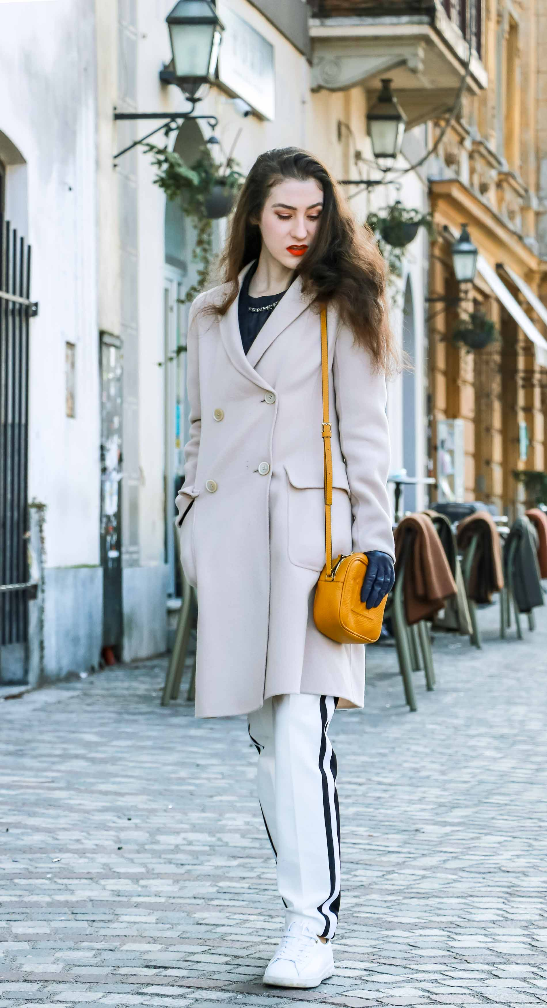 Fashion Blogger Veronika Lipar of Brunette from Wall Street dressed in white track pants with black side stripe from Escada, black silk blouse, off-white pastel double breasted coat from Weekend Max Mara, white leather sneakers from Diesel, yellow shoulder bag with logo from Escada while walking down the street in Ljubljana