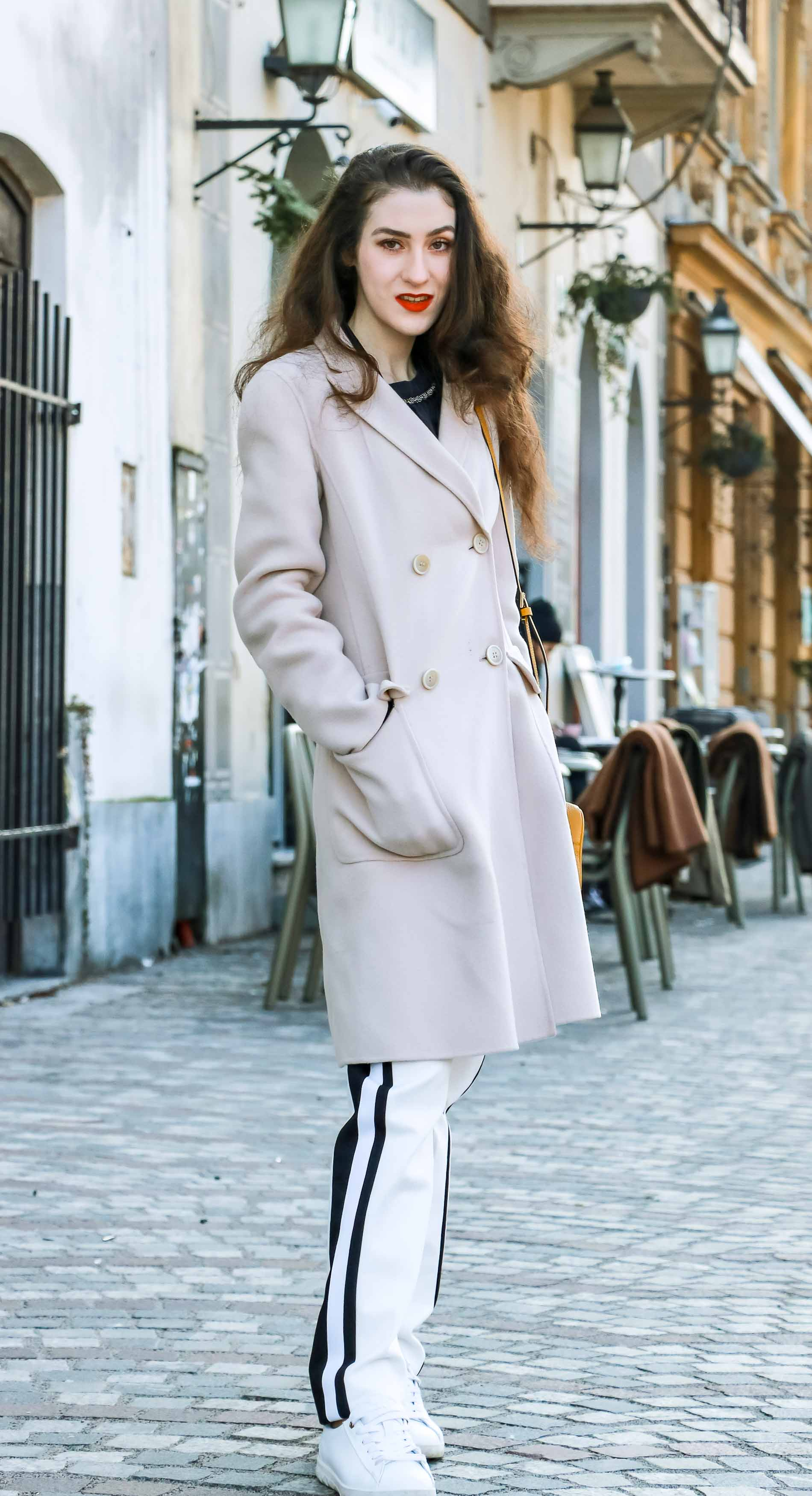 Fashion Blogger Veronika Lipar of Brunette from Wall Street wearing white track pants with black side stripe from Escada, black silk blouse, off-white pastel double breasted coat from Weekend Max Mara, white leather sneakers from Diesel, yellow logo shoulder bag with logo from Escada while walking down the street in Ljubljana