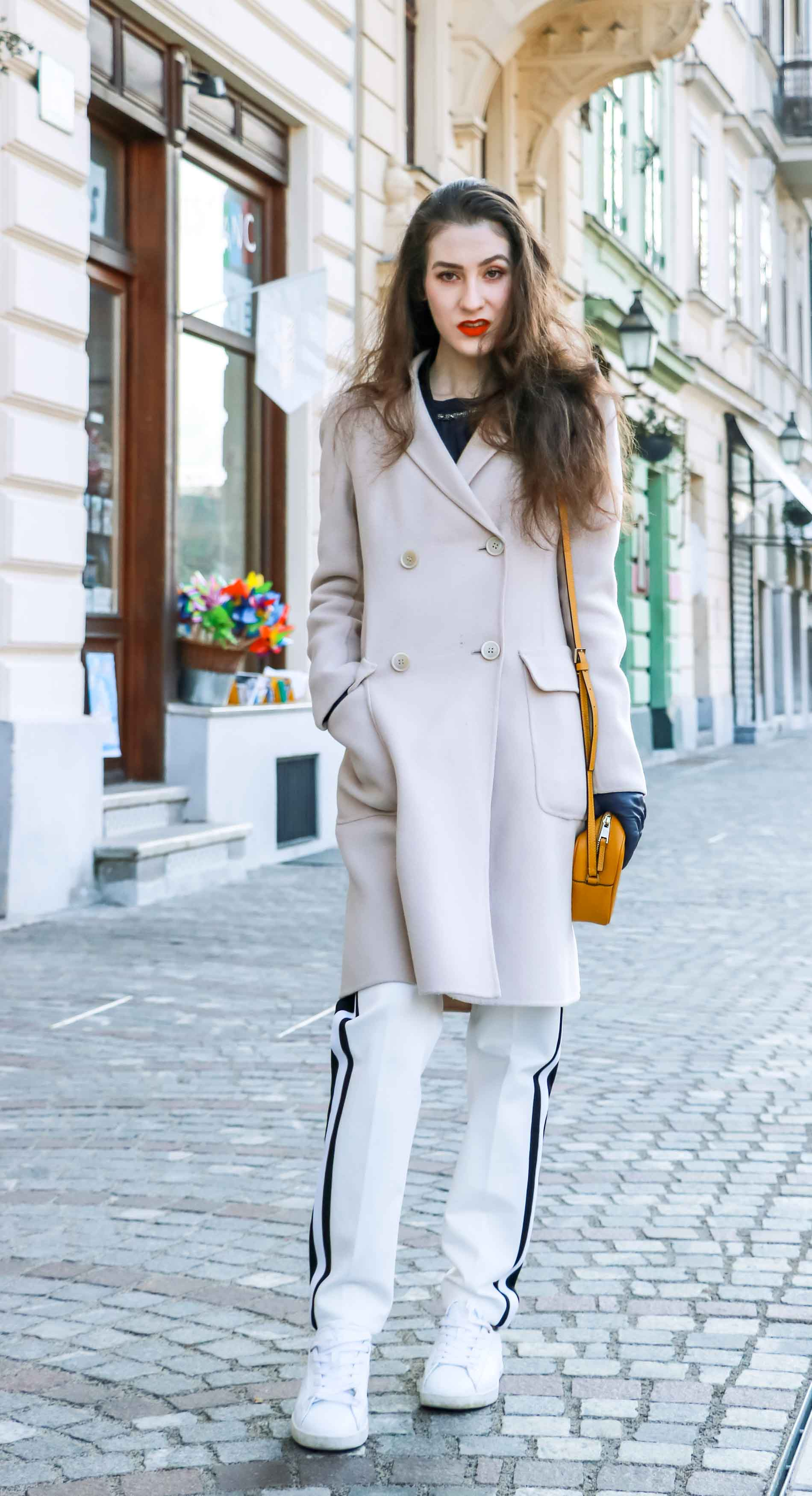 Fashion Blogger Veronika Lipar of Brunette from Wall Street dressed in white track pants with black side stripe from Escada, black silk blouse, off-white pastel double breasted coat from Weekend Max Mara, white leather sneakers from Diesel, yellow shoulder bag from Escada while standing on the street in Ljubljana