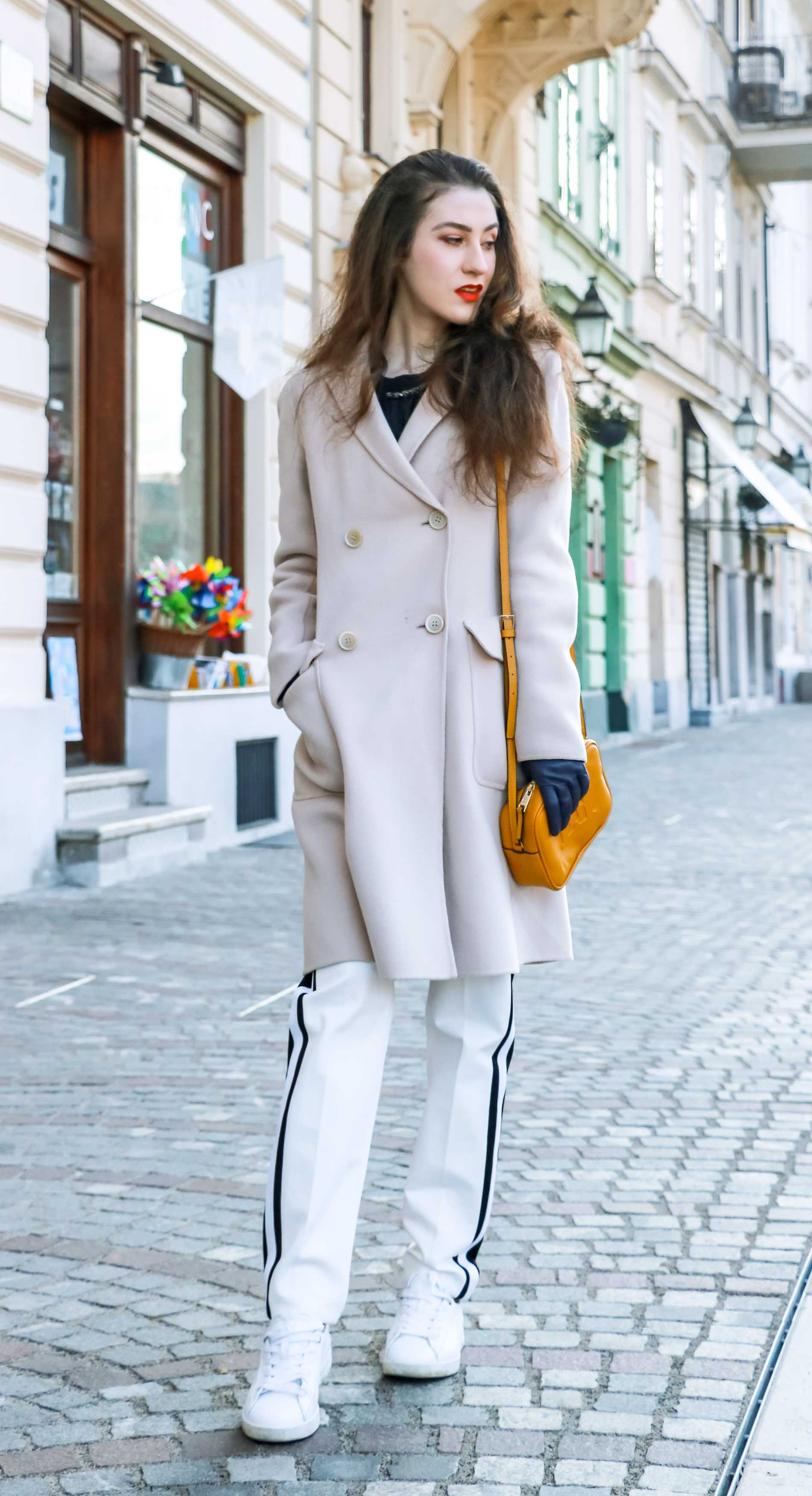 Fashion Blogger Veronika Lipar of Brunette from Wall Street wearing white track pants with black side stripe from Escada, black silk blouse, off-white pastel double breasted coat from Weekend Max Mara, white leather sneakers from Diesel, yellow shoulder bag from Escada while walking down the street in Ljubljana