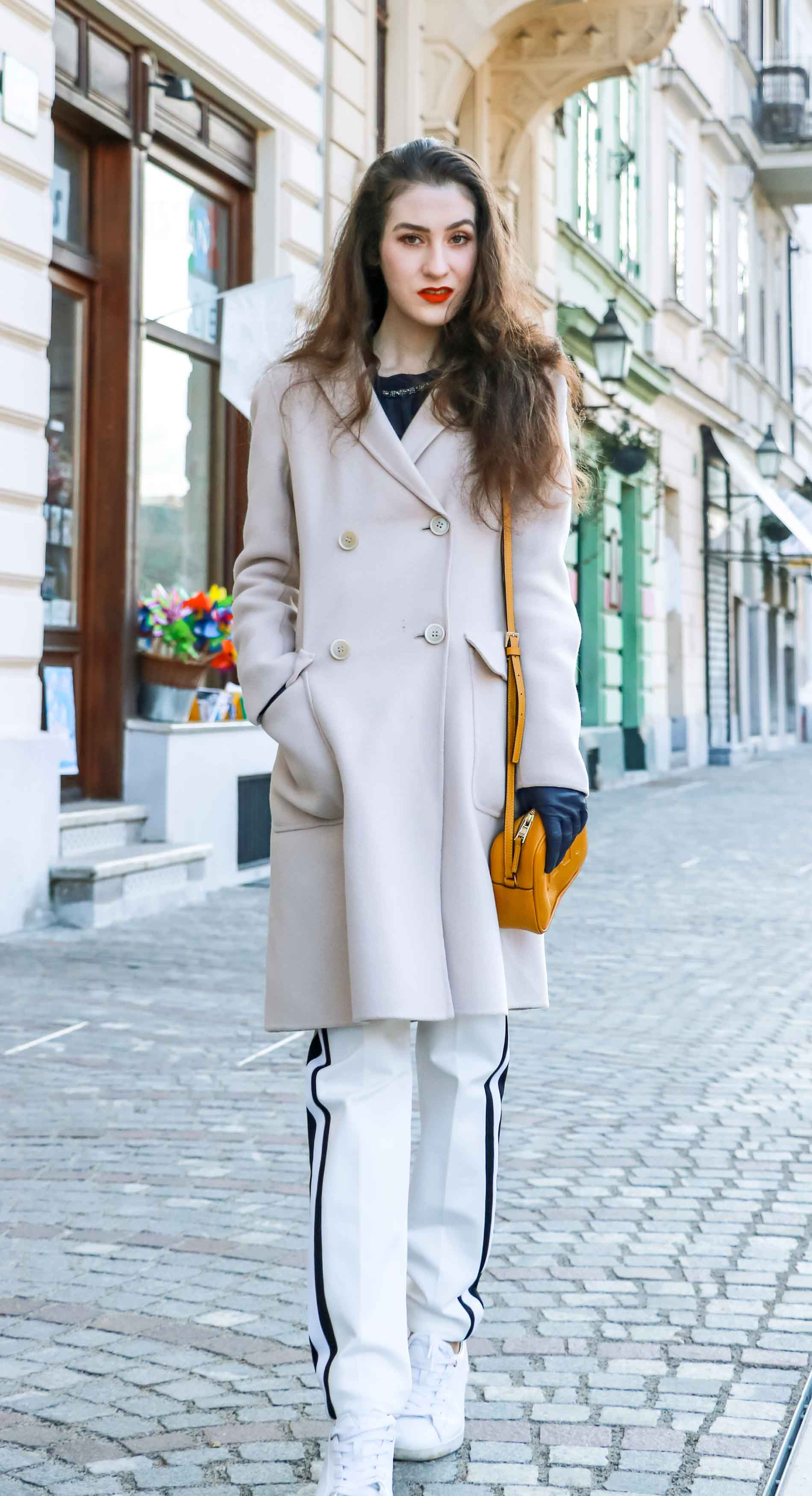 Fashion Blogger Veronika Lipar of Brunette from Wall Street dressed in white track pants with black side stripe from Escada, black silk blouse, off-white pastel double breasted coat from Weekend Max Mara, white leather sneakers from Diesel, yellow shoulder bag from Escada while walking down the street in Ljubljana