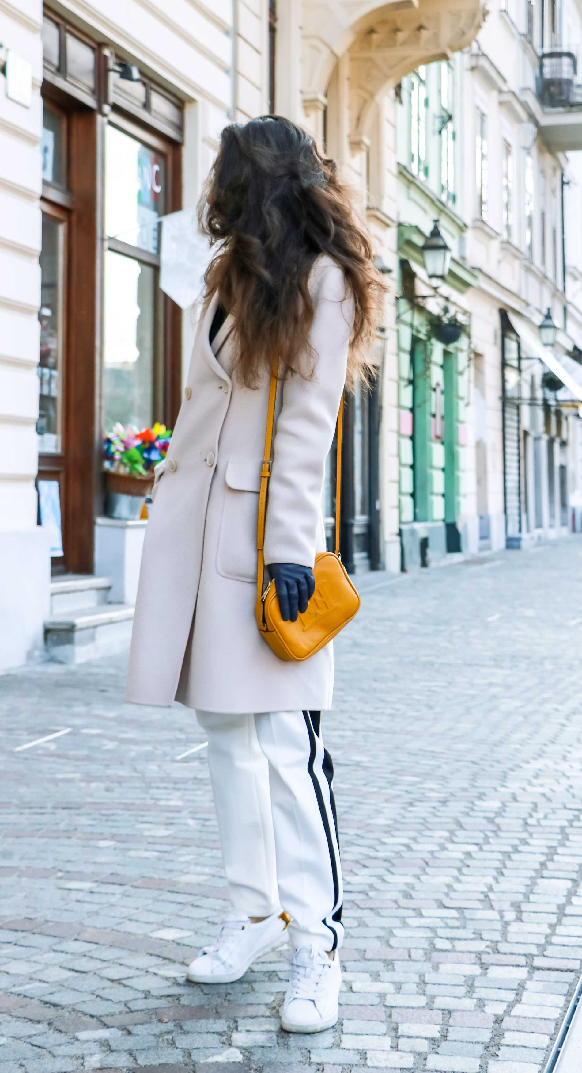 Fashion Blogger Veronika Lipar of Brunette from Wall Street wearing white track pants with black side stripe from Escada, black silk blouse, off-white pastel double breasted coat from Weekend Max Mara, white leather sneakers from Diesel, yellow shoulder bag from Escada while standing on the street in Ljubljana