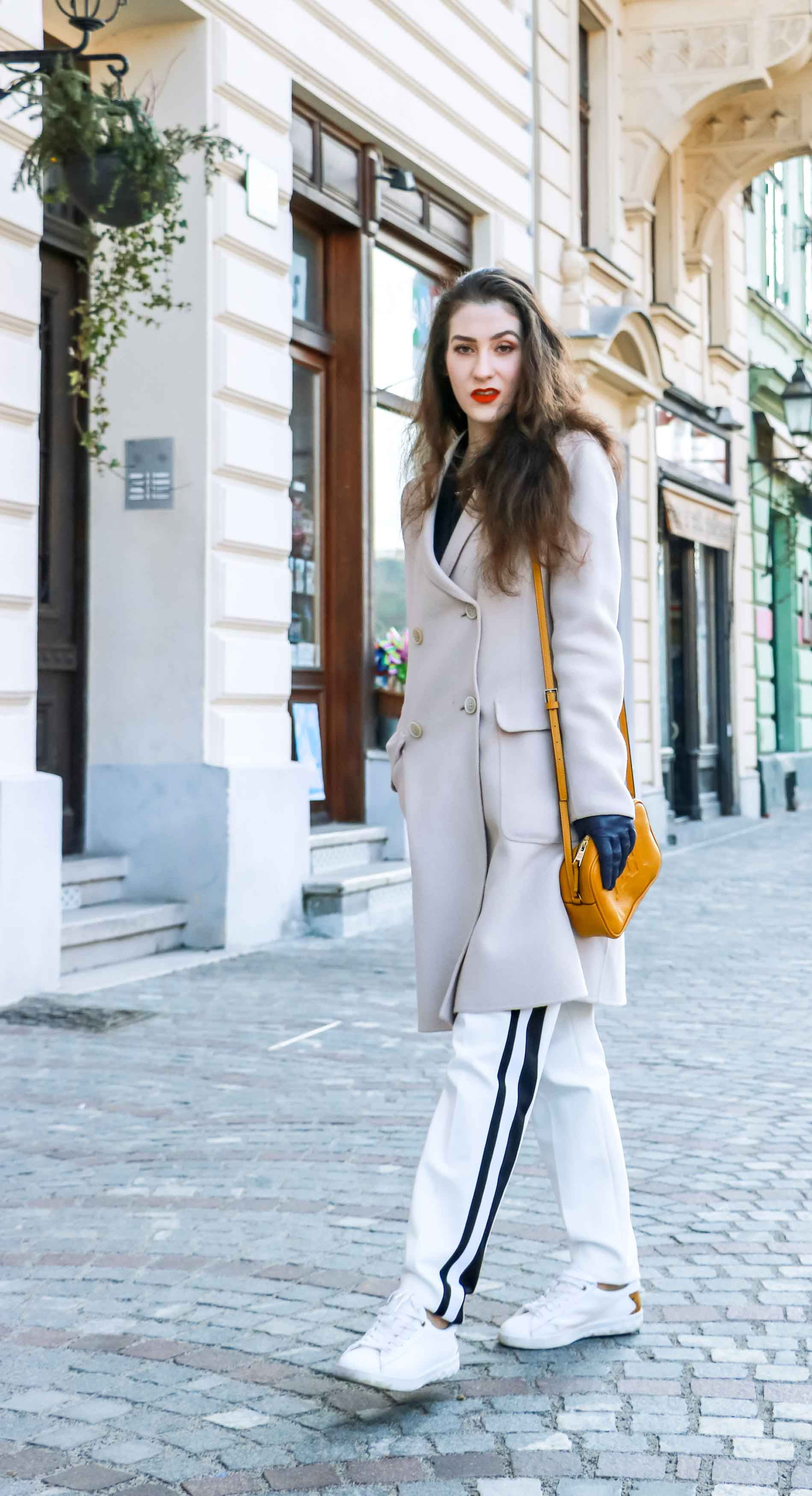 Fashion Blogger Veronika Lipar of Brunette from Wall Street wearing white track pants with black side stripe from Escada, black silk blouse, off-white pastel double breasted coat from Weekend Max Mara, white leather sneakers from Diesel, yellow shoulder bag with logo from Escada while walking down the street in Ljubljana