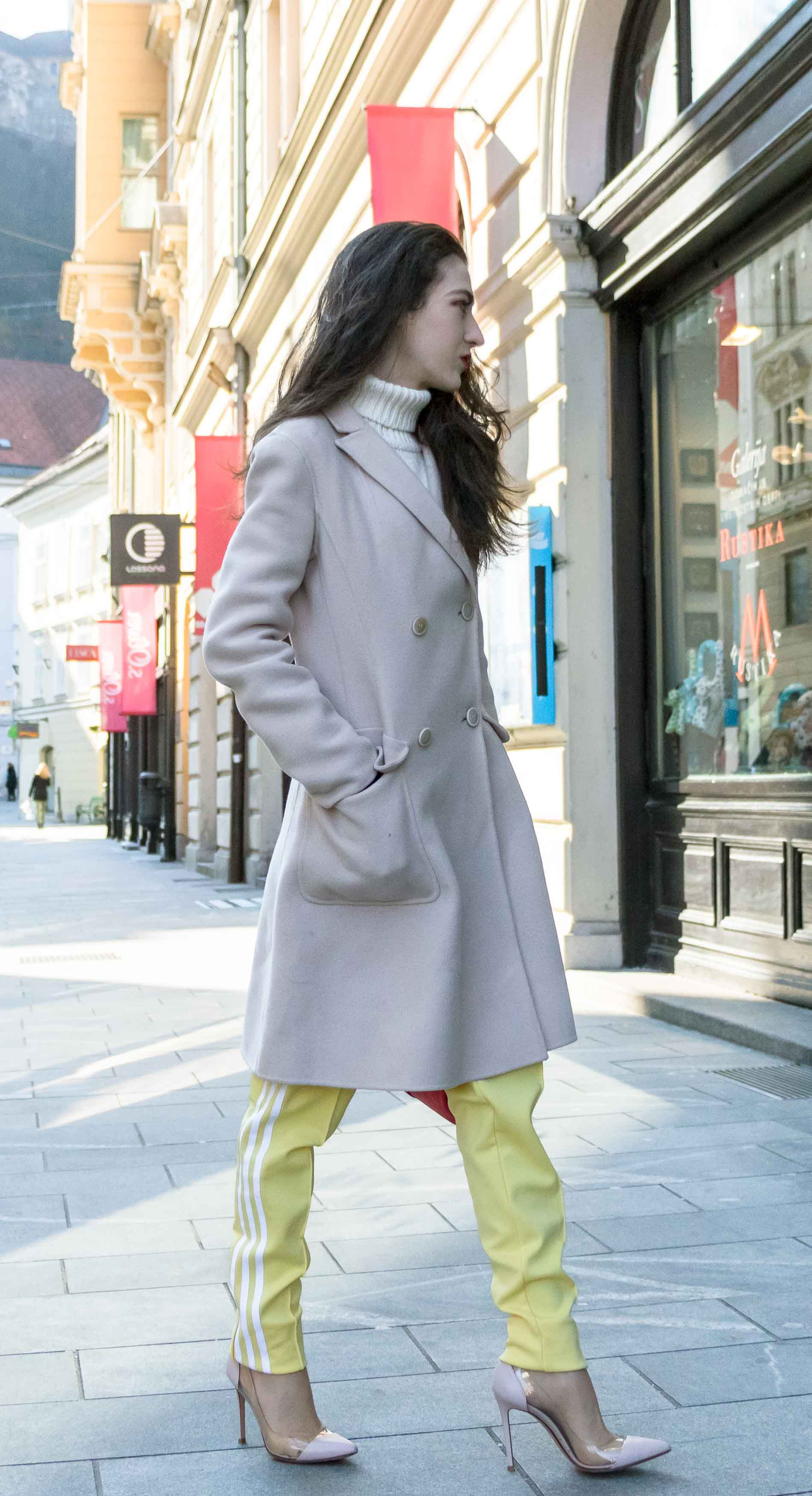 Fashion Blogger Veronika Lipar of Brunette from Wall Street wearing yellow track pants with white stripes from Adidas, white turtleneck knit sweater, off-white pastel double breasted coat from Weekend Max Mara, blush powder transparent plexiglass shoes from Gianvito Rossi, pink top handle bag from See by Chloe while walking on the street in Ljubljana