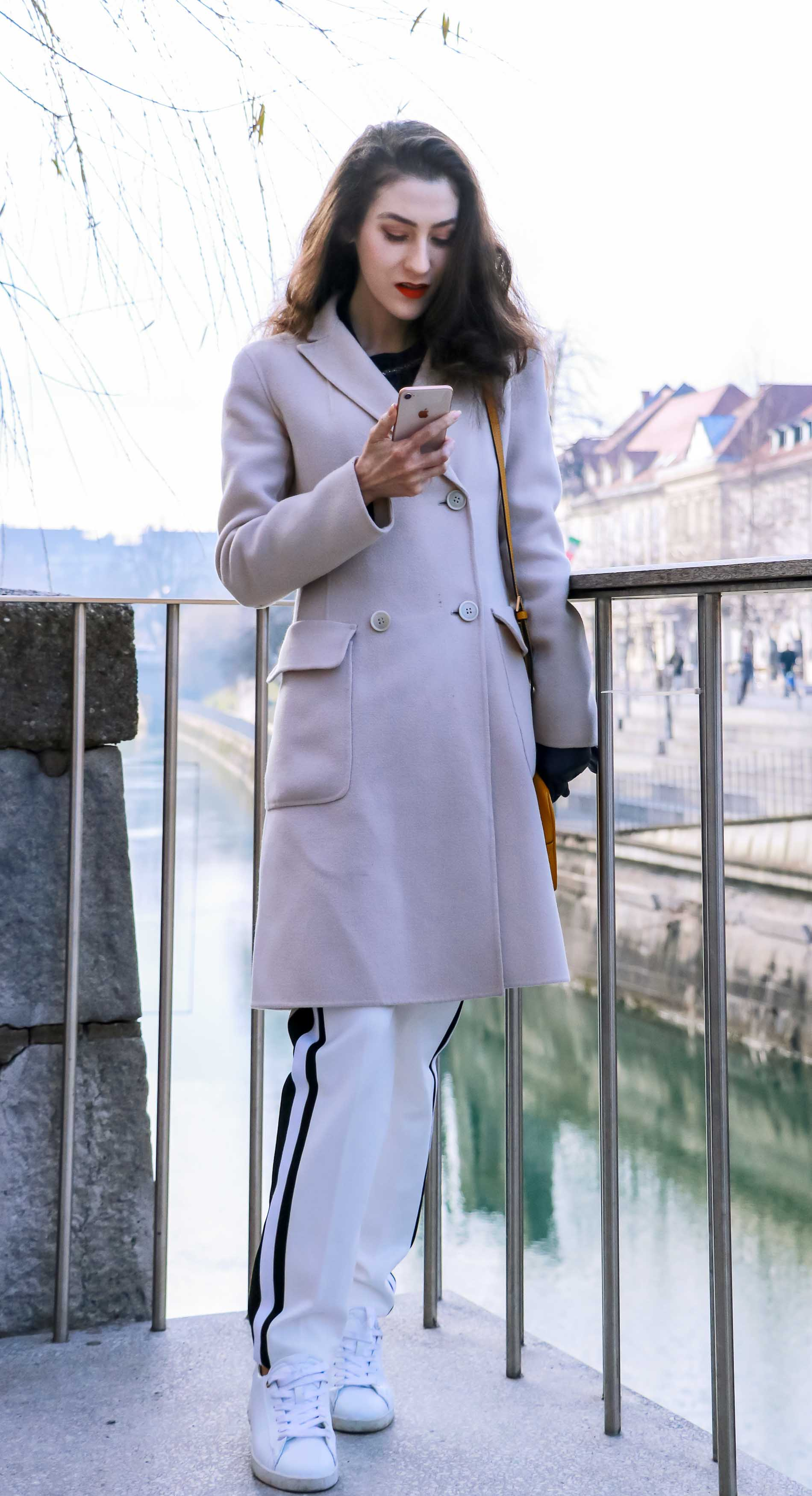 Fashion Blogger Veronika Lipar of Brunette from Wall Street dressed in white track pants with black side stripe from Escada, black silk blouse, off-white pastel double breasted coat from Weekend Max Mara, white leather sneakers from Diesel, yellow shoulder bag from Escada while checking iPhone