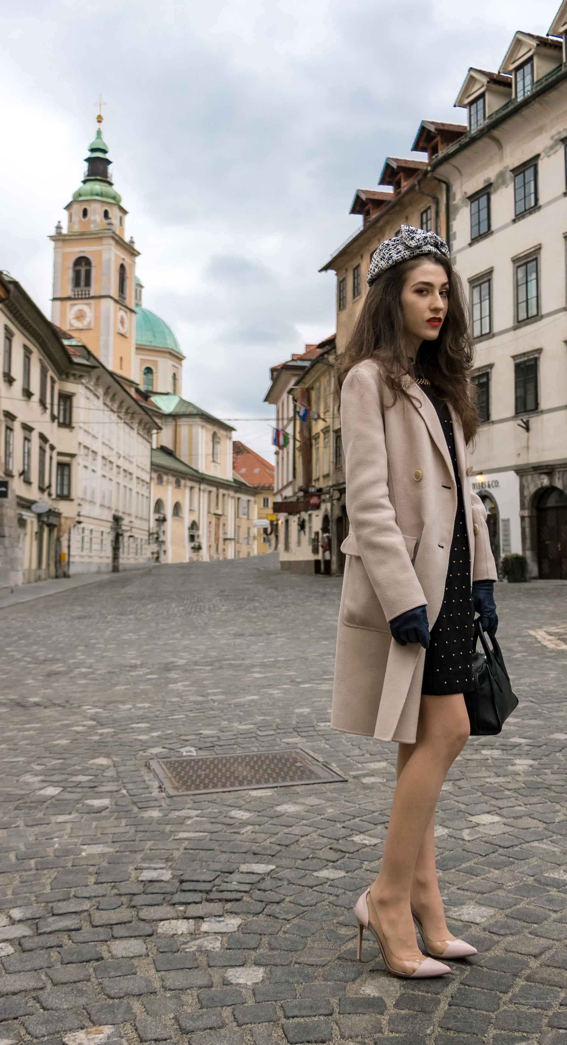 Fashion Blogger Veronika Lipar of Brunette from Wall Street wearing headwear, Weekend Maxmara off-white pastel coat, Gianvito Rossi plexi pumps, small black top handle bag on the street for Easter holidays before Sunday Mass
