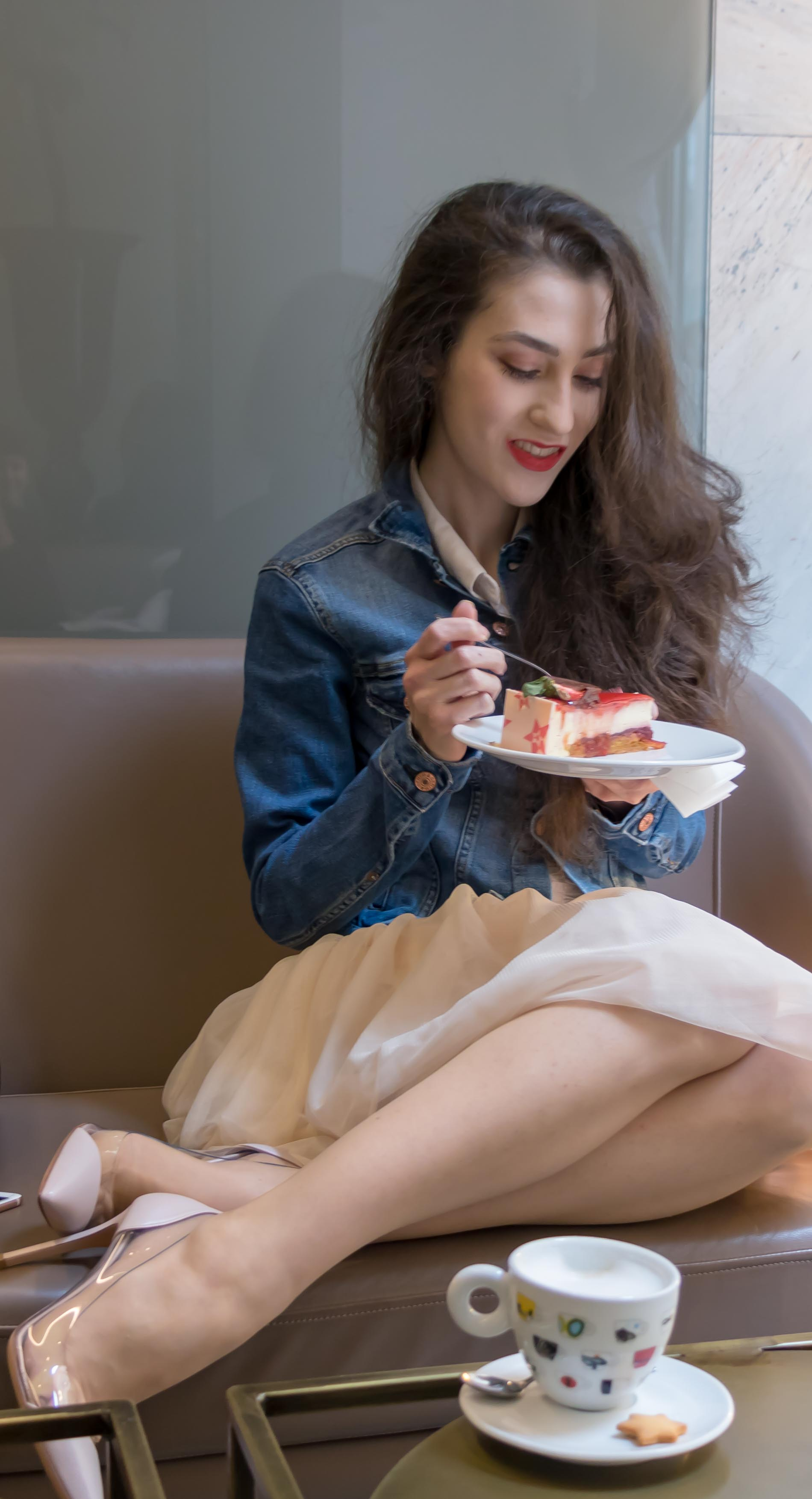 Fashion Blogger Veronika Lipar of Brunette from Wall Street wearing blush Gianvito Rossi Plexi 100 leather and PVC pump shoes, blush tulle skirt from Zara, blue denim jacket from H&M while eating cake