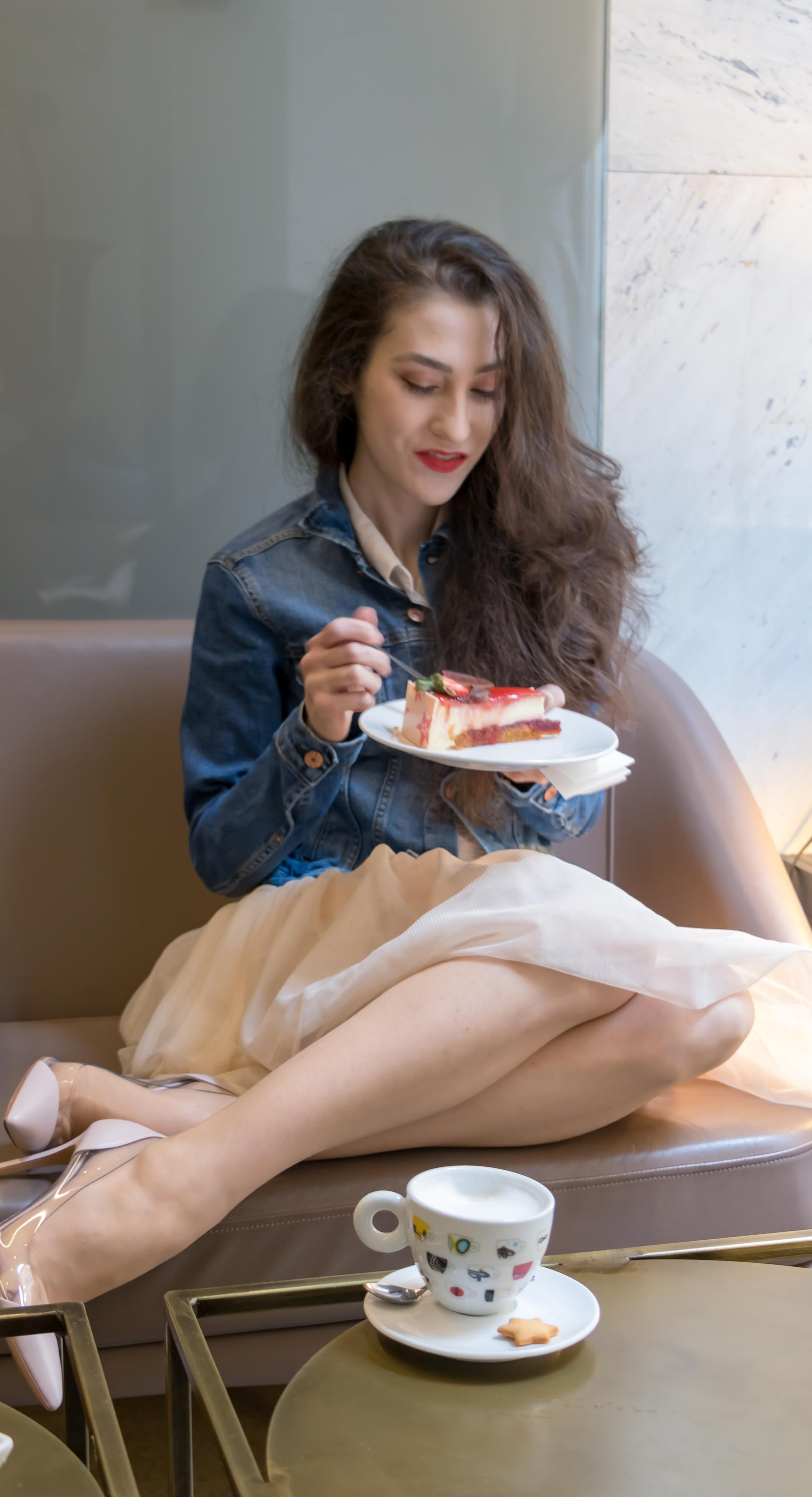 Fashion Blogger Veronika Lipar of Brunette from Wall Street wearing blush Gianvito Rossi Plexi 100 leather and PVC pump shoes, blush tulle Zara skirt, blue denim jacket from H&M while eating cake