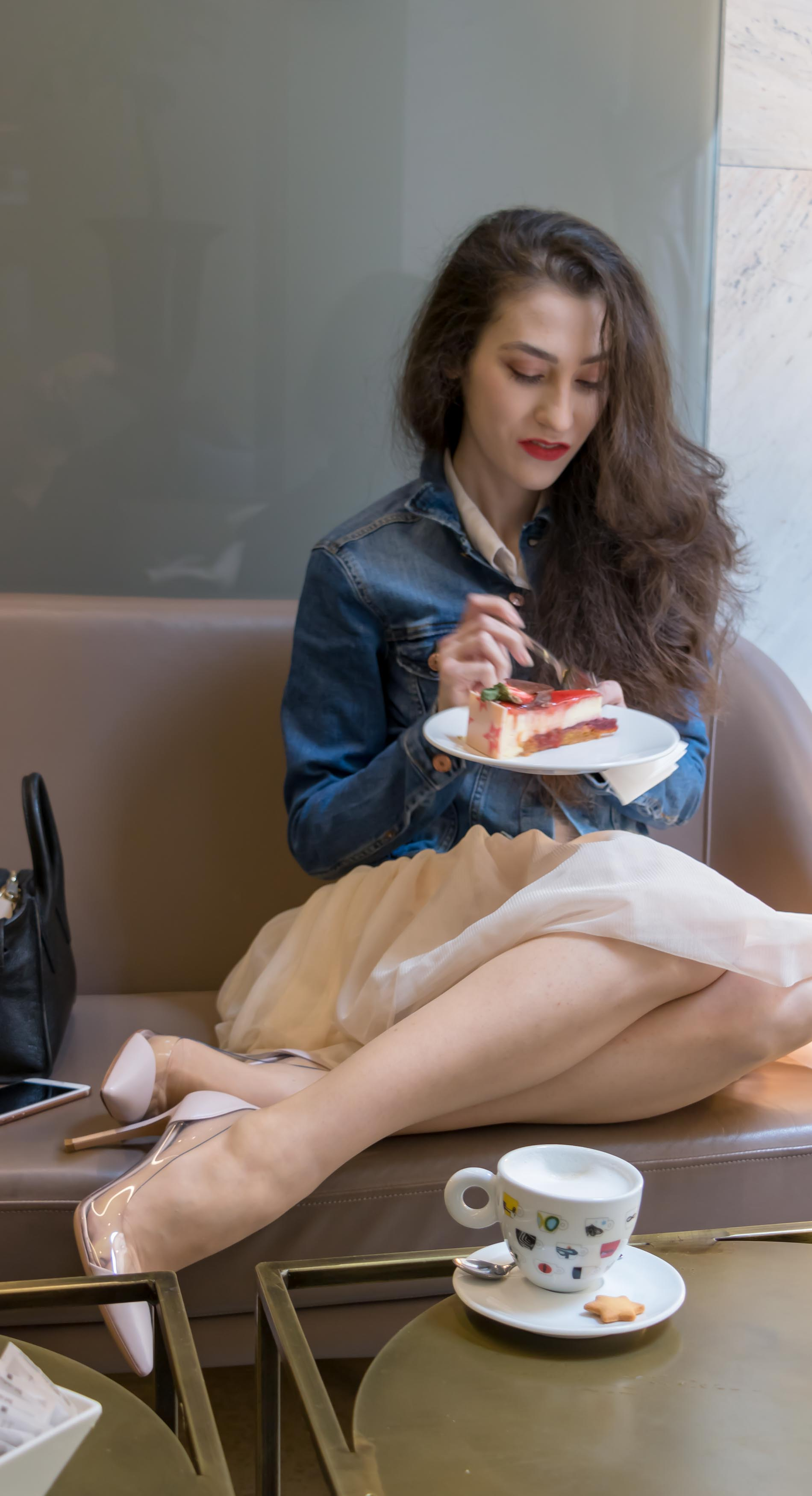 Fashion Blogger Veronika Lipar of Brunette from Wall Street dressed in blush Gianvito Rossi Plexi 100 leather and PVC pump shoes, blush tulle Zara skirt, blue denim jacket from H&M while having a cake