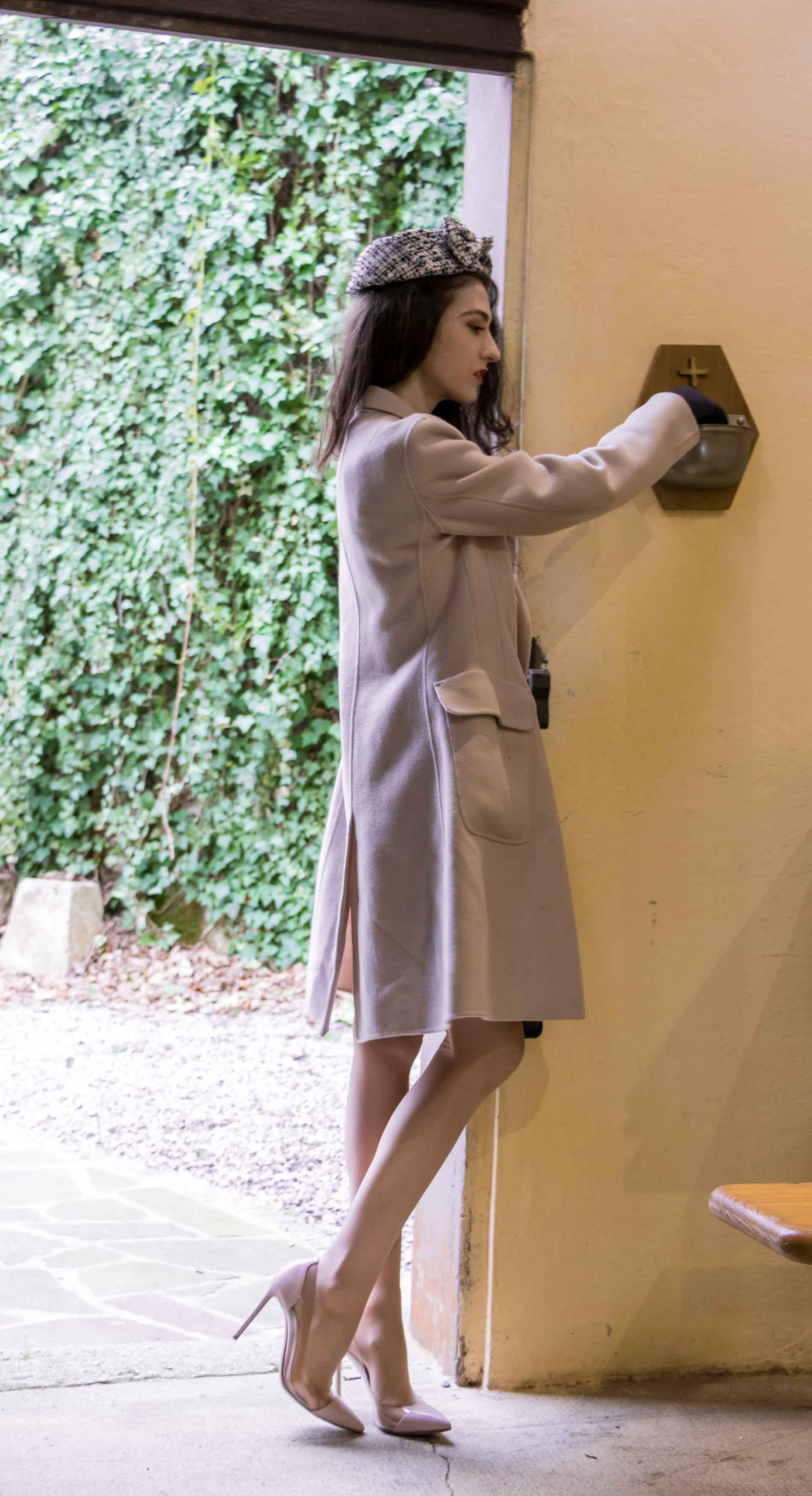 Fashion Blogger Veronika Lipar of Brunette from Wall Street wearing haeadpiece, Weekend Maxmara off-white pastel coat, Gianvito Rossi plexi pumps, small black top handle bag to Sunday Mass