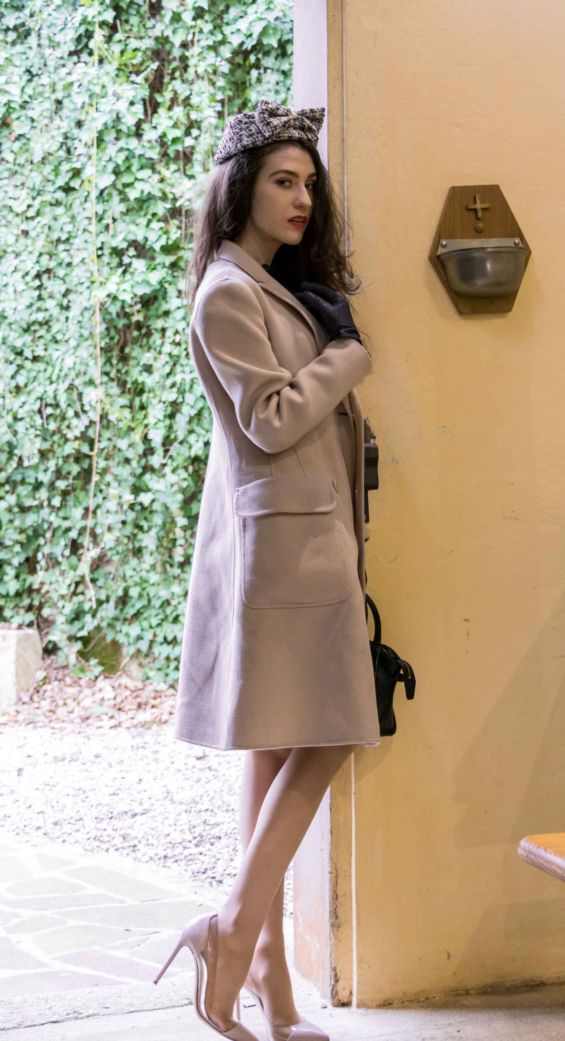 Fashion Blogger Veronika Lipar of Brunette from Wall Street dressed in Weekend Maxmara off-white pastel coat, Gianvito Rossi plexi pumps, small black top handle bag and headpiece to Sunday Mass