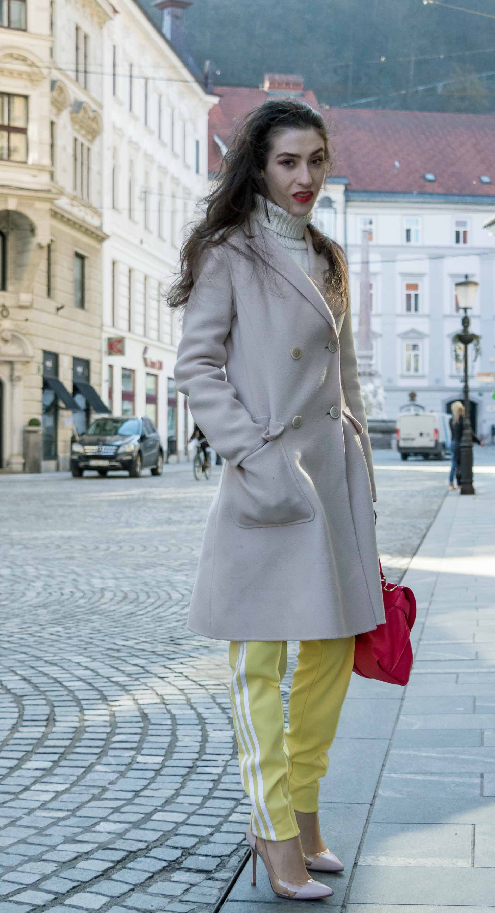 Fashion Blogger Veronika Lipar of Brunette from Wall Street wearing yellow track pants with white stripes from Adidas, white turtleneck knit sweater, off-white pastel double breasted coat from Weekend Max Mara, blush powder transparent plexi shoes from Gianvito Rossi, pink top handle bag from See by Chloe while standing on the street in Ljubljana