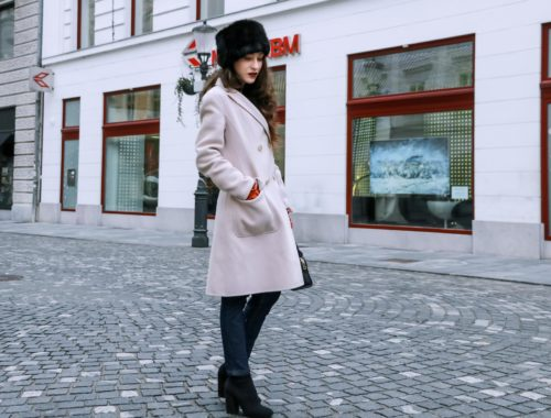 Fashion Blogger Veronika Lipar of Brunette from Wall Street wearing black faux fur hat from Amazon, off-white pastel double-breasted coat from Weekend MaxMara, dark indigo denim tapered jeans from A.P.C., small black top handle bag, red leather gloves, black sock boots from Elena Iachi when it's freezing outside
