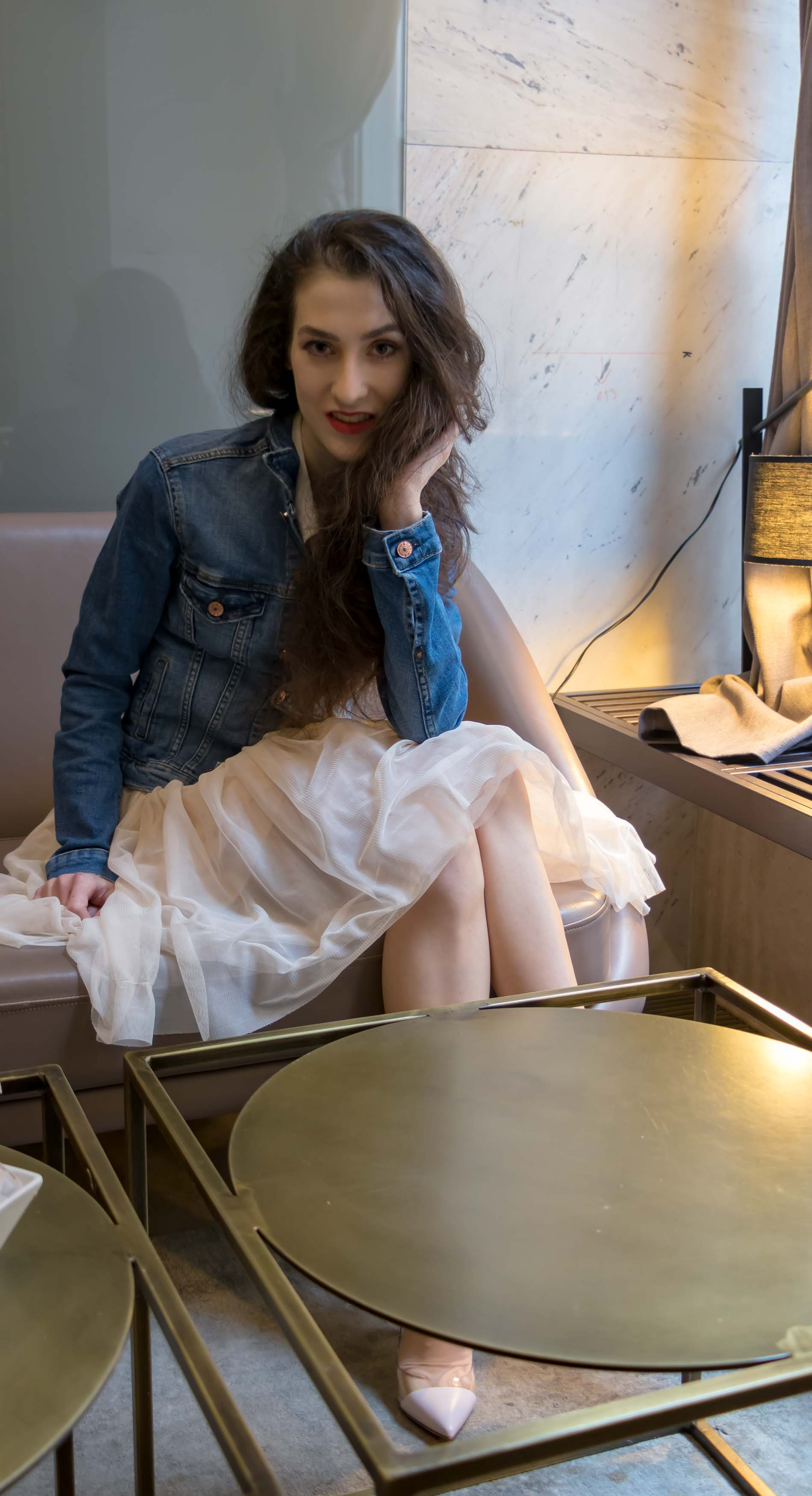 Fashion Blogger Veronika Lipar of Brunette from Wall Street dressed in blush Gianvito Rossi Plexi 100 leather and PVC pump shoes, blush tulle skirt from Zara, blue denim jacket from H&M while sitting on sofa