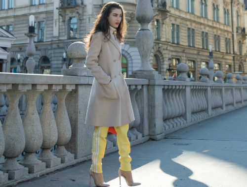 Fashion Blogger Veronika Lipar of Brunette from Wall Street wearing yellow track pants with white stripes from Adidas, white turtleneck knit sweater, off-white pastel double breasted coat from Weekend Max Mara, blush powder transparent plexiglass shoes from Gianvito Rossi, pink top handle bag from See by Chloe while standing on the bridge in Ljubljana