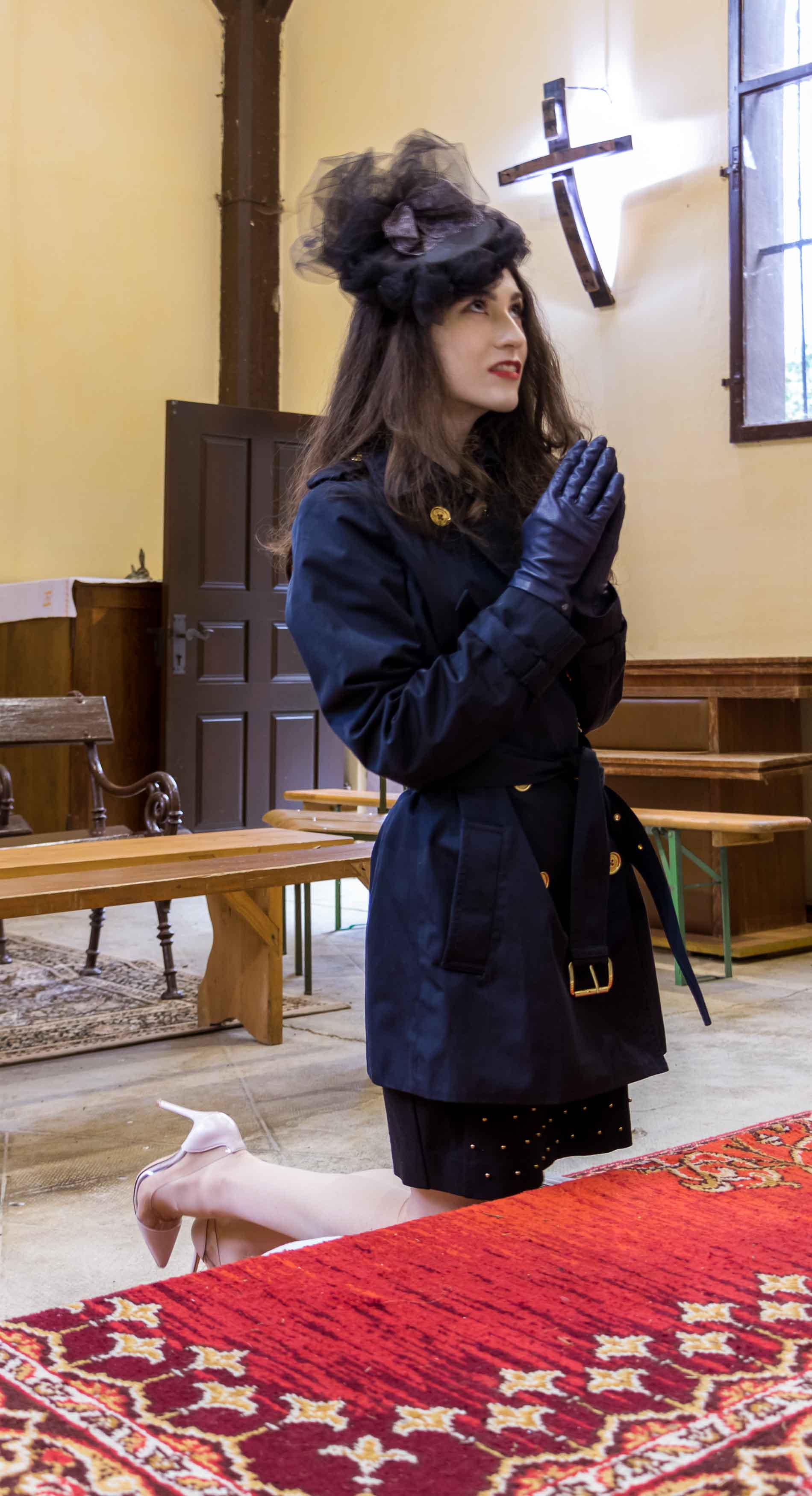 Fashion Blogger Veronika Lipar of Brunette from Wall Street dressed in blue Burberry trench coat, Gianvito Rossi plexi pumps, small black white shoulder bag and hat in church praying