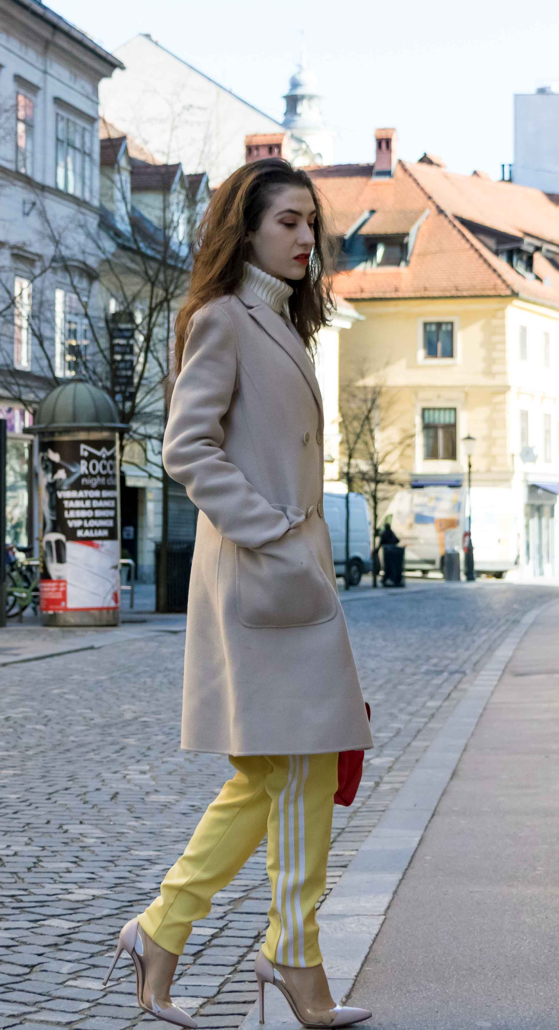 Fashion Blogger Veronika Lipar of Brunette from Wall Street wearing yellow track pants with white stripes from Adidas, white turtleneck knit sweater, off-white pastel double breasted coat from Weekend Max Mara, blush powder transparent plexi pumps shoes from Gianvito Rossi, pink top handle bag from See by Chloe while crossing the street in Ljubljana on a cold spring day