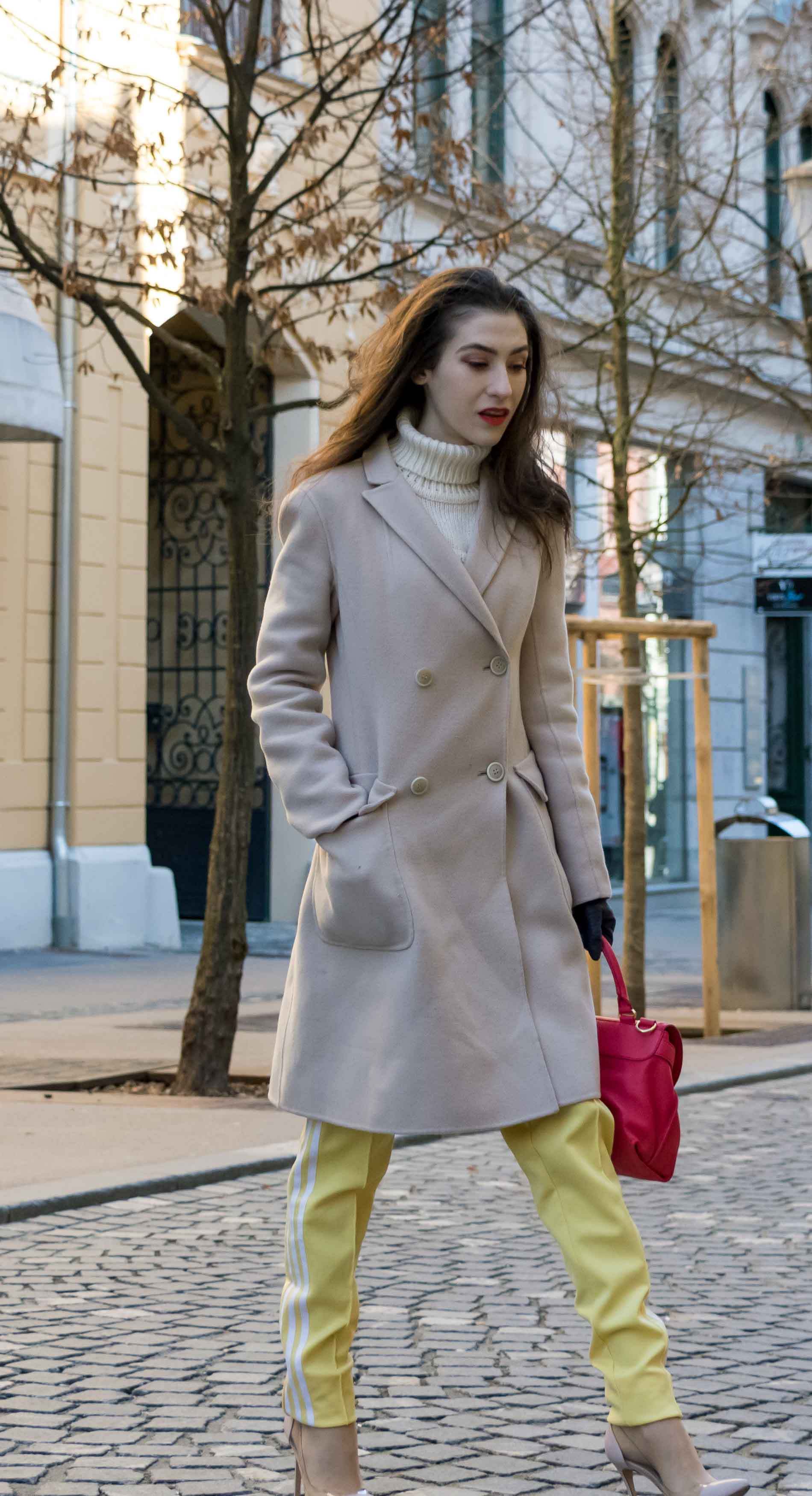 Fashion Blogger Veronika Lipar of Brunette from Wall Street dressed in yellow track pants with white stripes from Adidas, white turtleneck knit sweater, off-white pastel double breasted coat from Weekend Max Mara, blush powder transparent plexi pumps shoes from Gianvito Rossi, pink top handle bag from See by Chloe while crossing the street in Ljubljana on a cold spring day