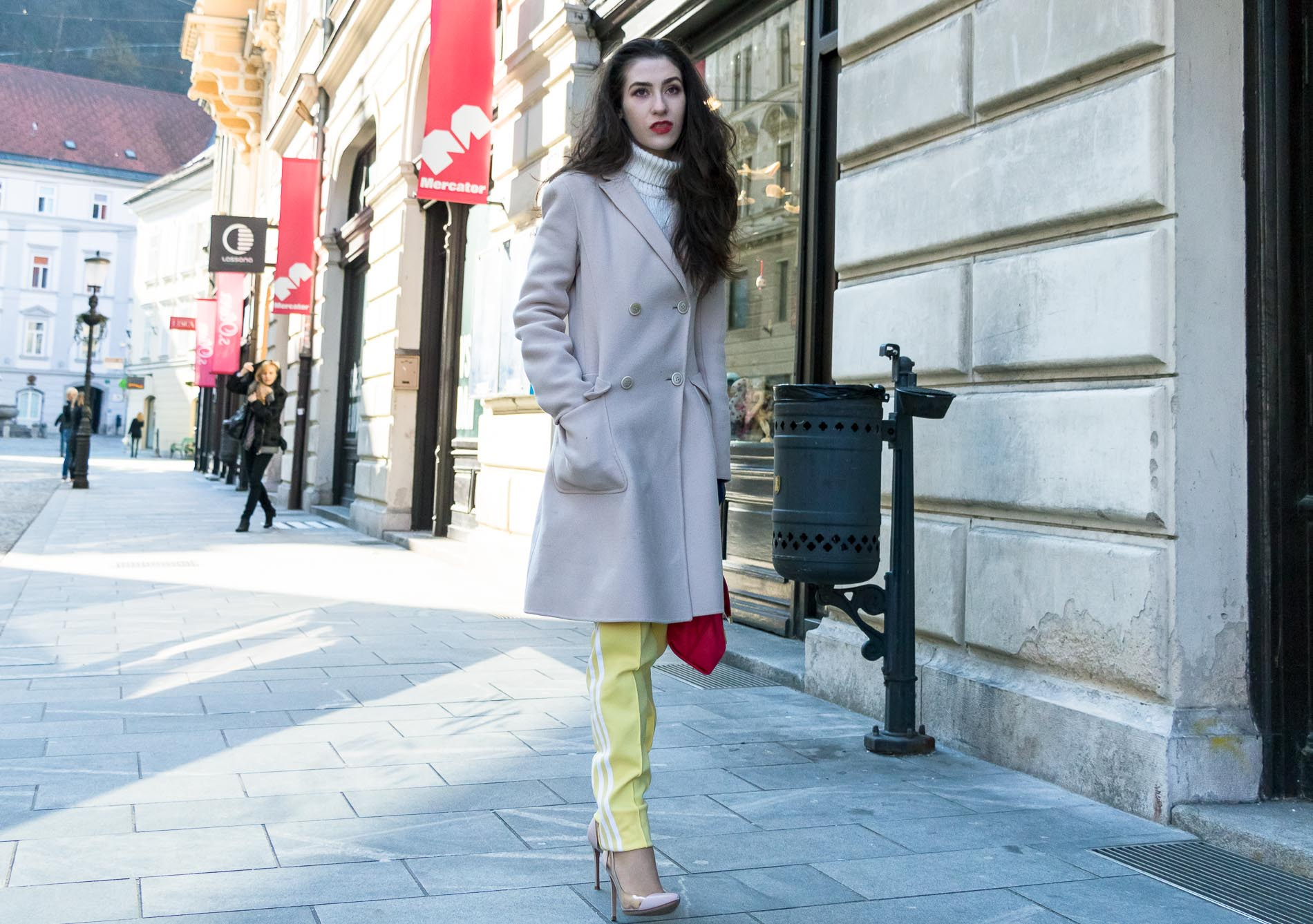 Fashion Blogger Veronika Lipar of Brunette from Wall Street wearing yellow track pants with white stripes from Adidas, white turtleneck knit sweater, off-white pastel double breasted coat from Weekend Max Mara, blush powder transparent plexi shoes from Gianvito Rossi, pink top handle bag from See by Chloe while walking down the street in Ljubljana