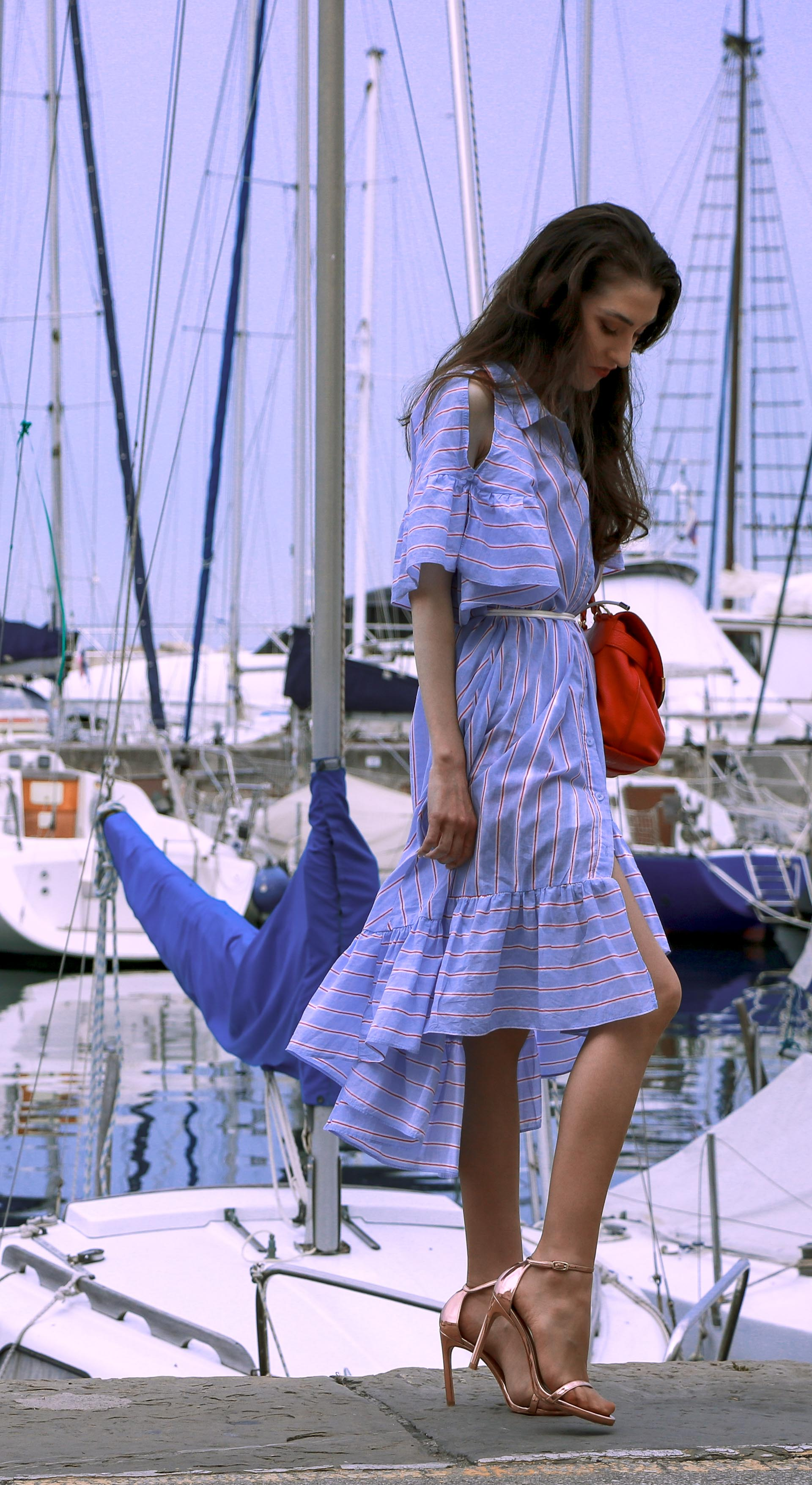 Beautiful Slovenian fashion blogger Veronika Lipar of Brunette from Wall Street dressed in striped cold shoulder shirt dress with rope belt Stuart Weitzman nudist song sandals pink See by Chloe top handle bag standing by the sailing boats